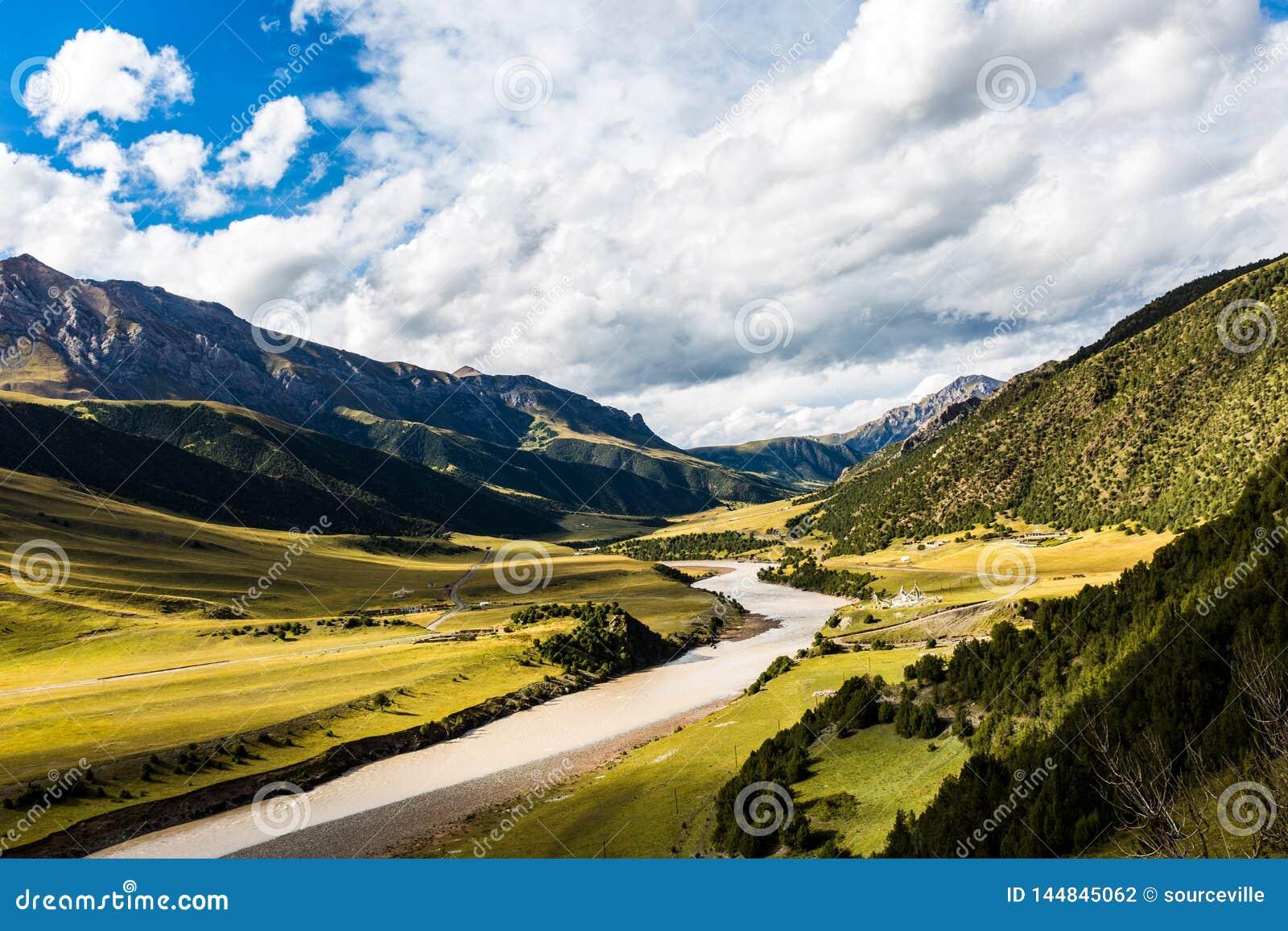 Aardlandschap van het overweldigen van bergen en water onder duidelijke blauwe hemel met wolken