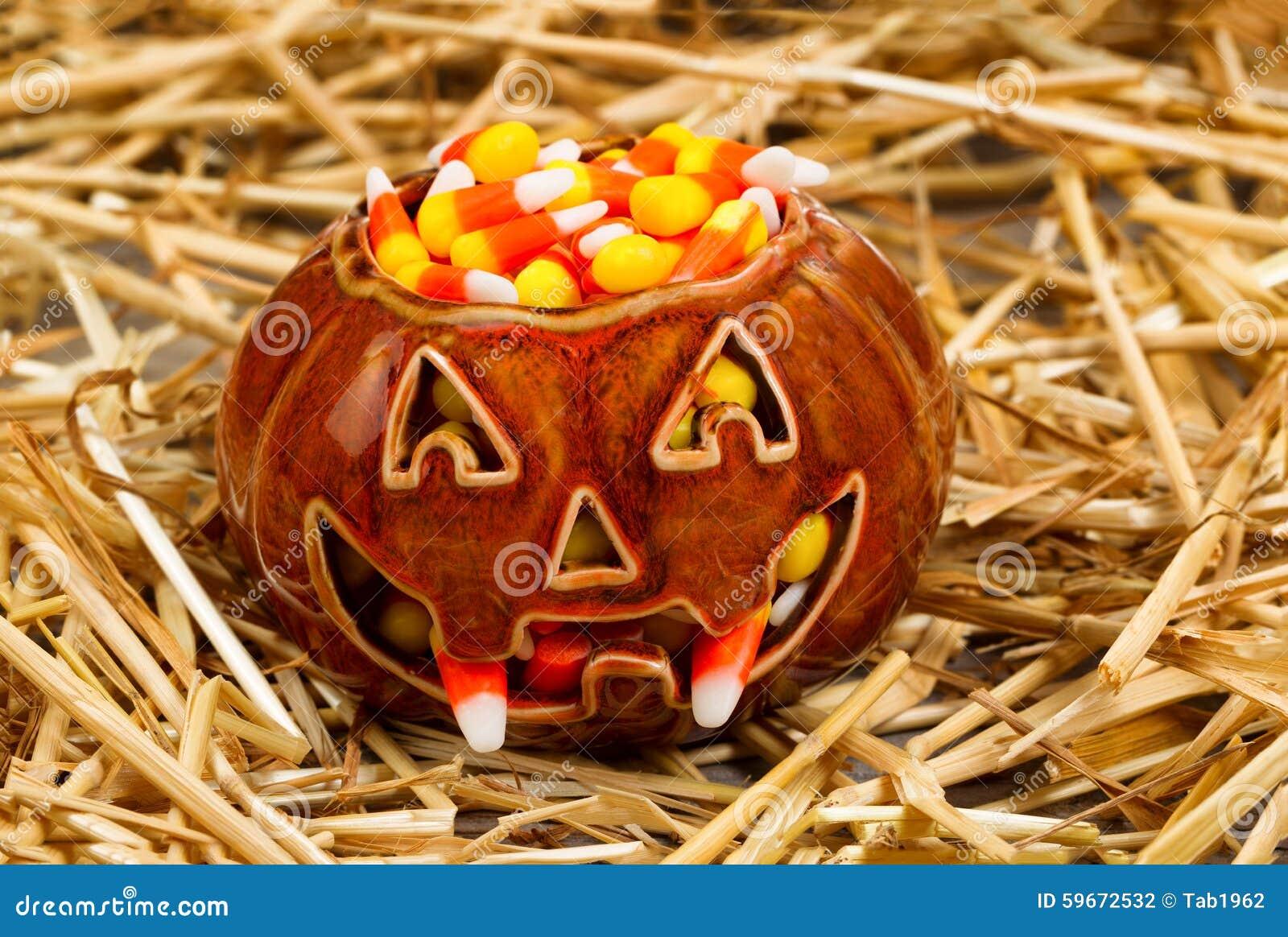 A abóbora assustador encheu-se com o milho de doces na palha