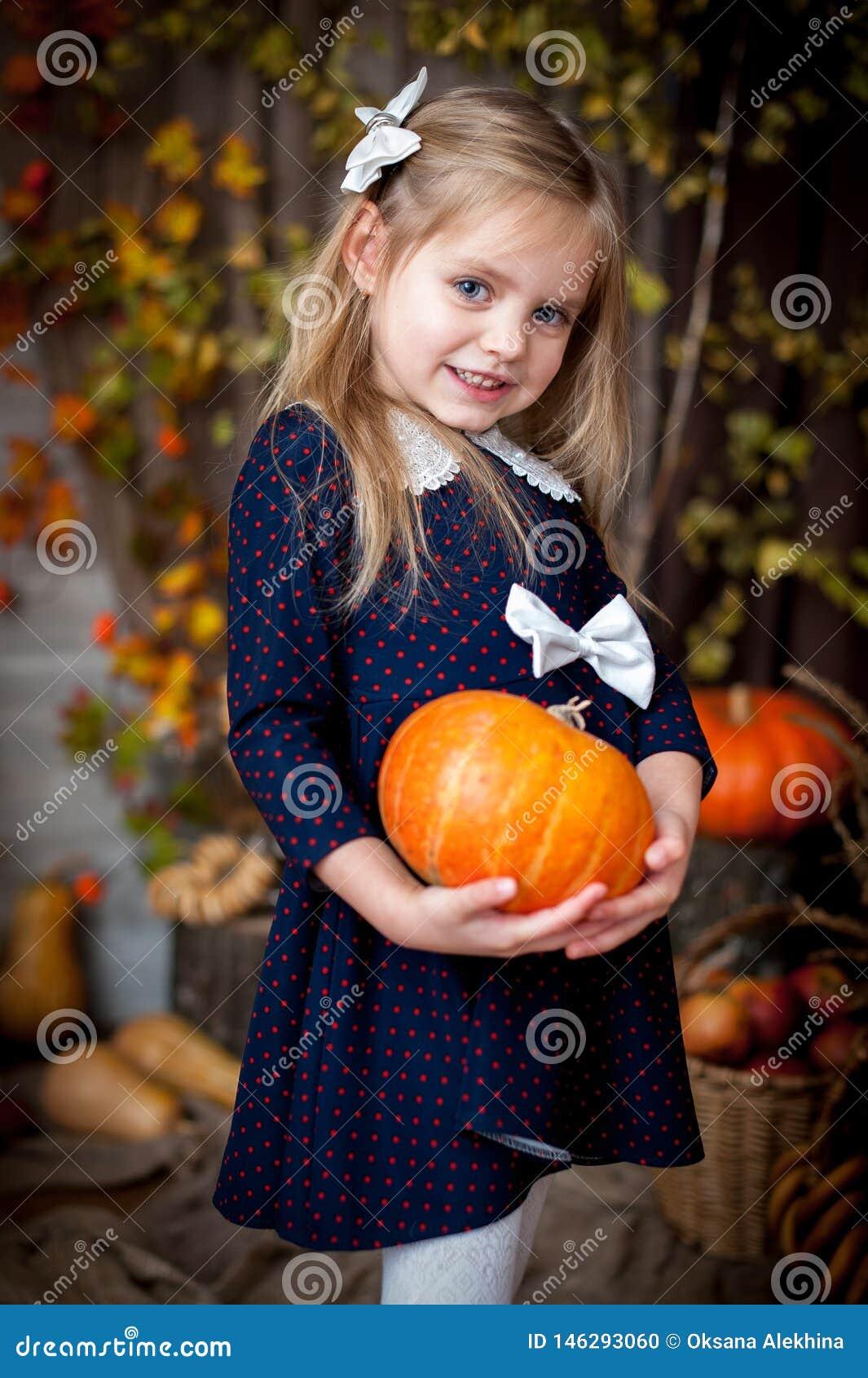 Abóbora da terra arrendada da menina no interior do outono