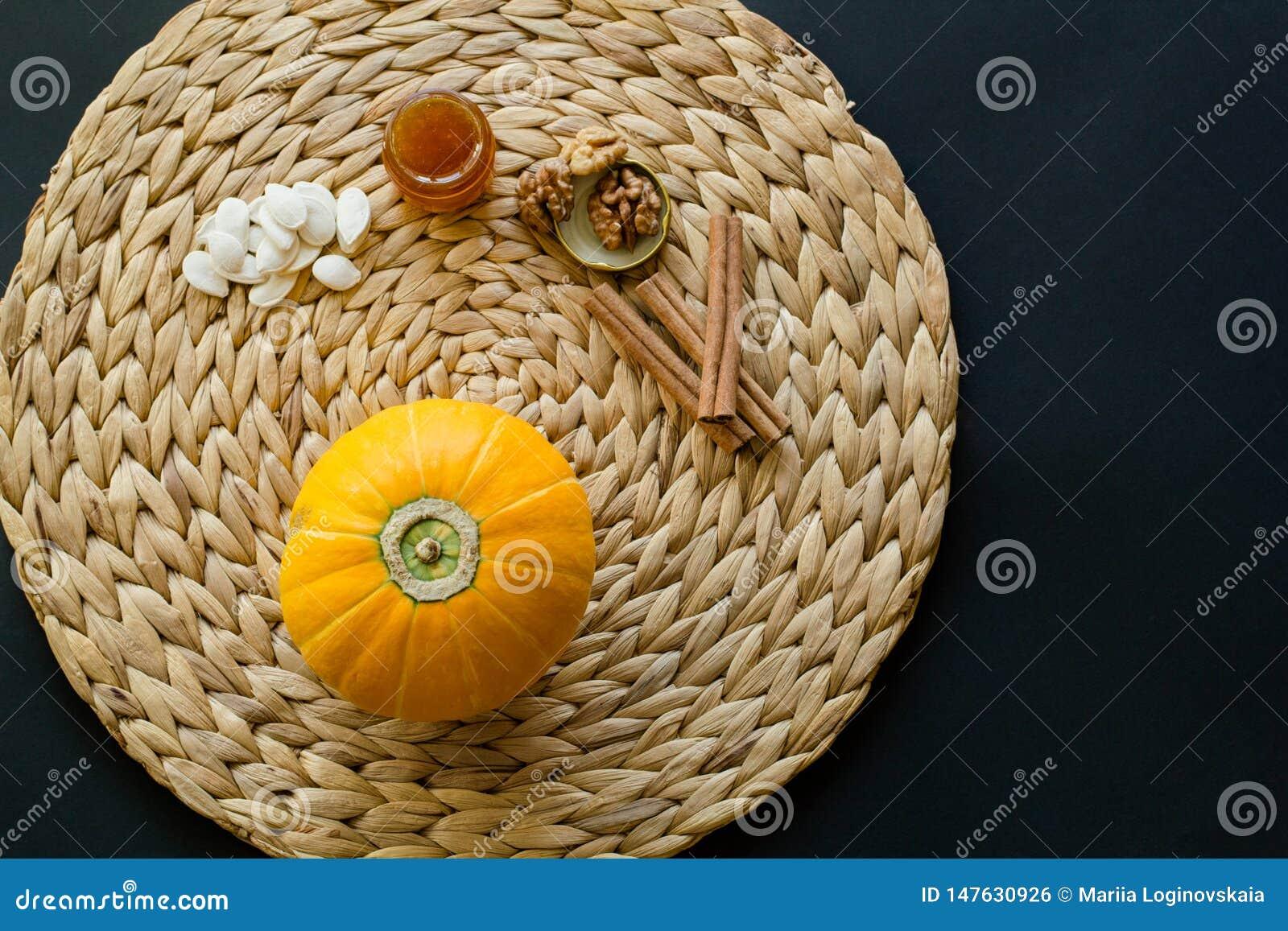 A abóbora pequena com sementes, pouca lata de vidro do mel, nozes e varas de canela em uma esteira/guardanapo do círculo fez do j