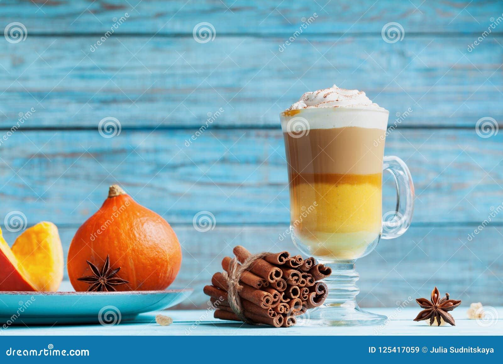 A abóbora temperou o latte ou o café no vidro na tabela rústica de turquesa Bebida quente do outono, da queda ou do inverno