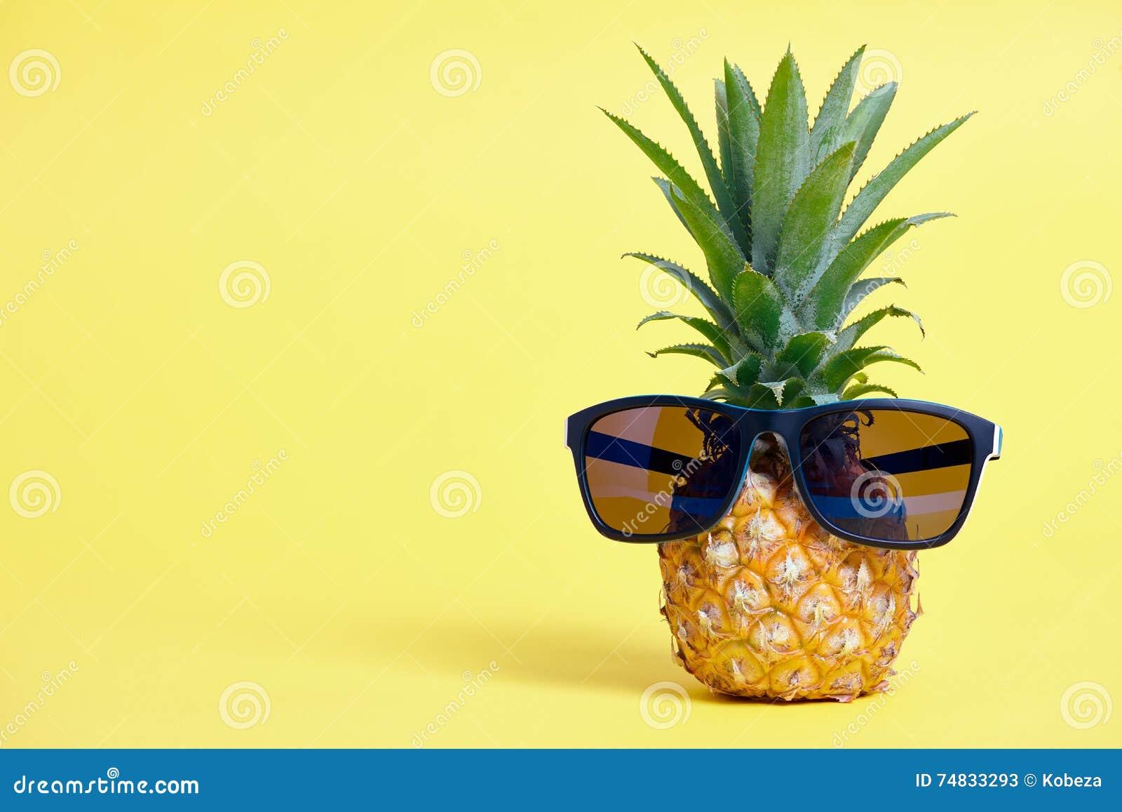 Abacaxi com os óculos de sol no fundo amarelo