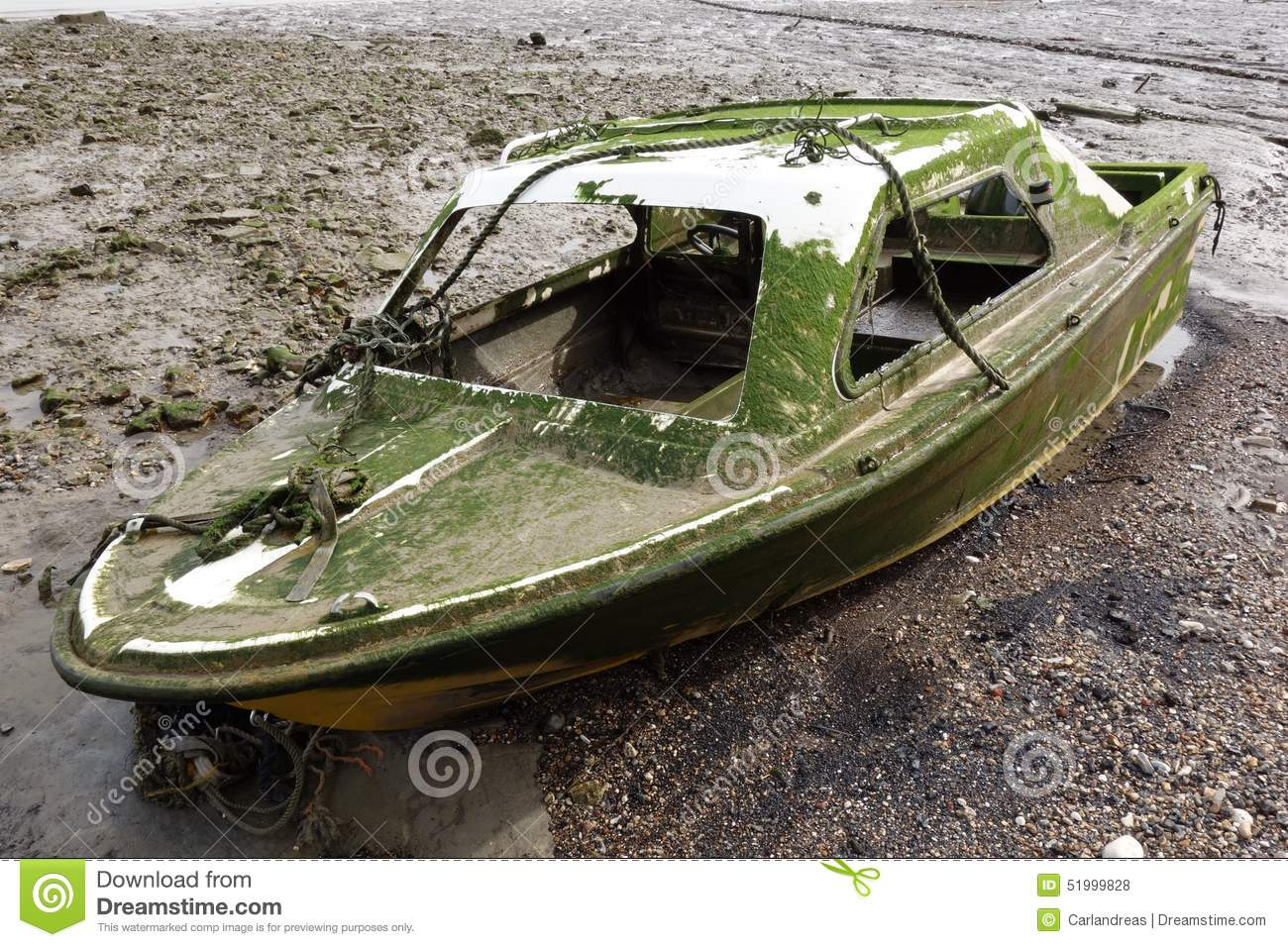 Abandoned wreck of a small modern fibreglass motorboat left beached on ...