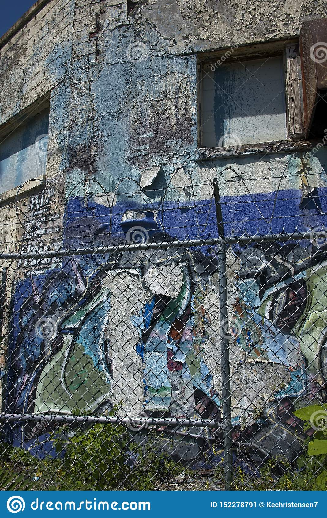 Abandoned Building with Peeling Paint and Barbed Wire Coil Fence