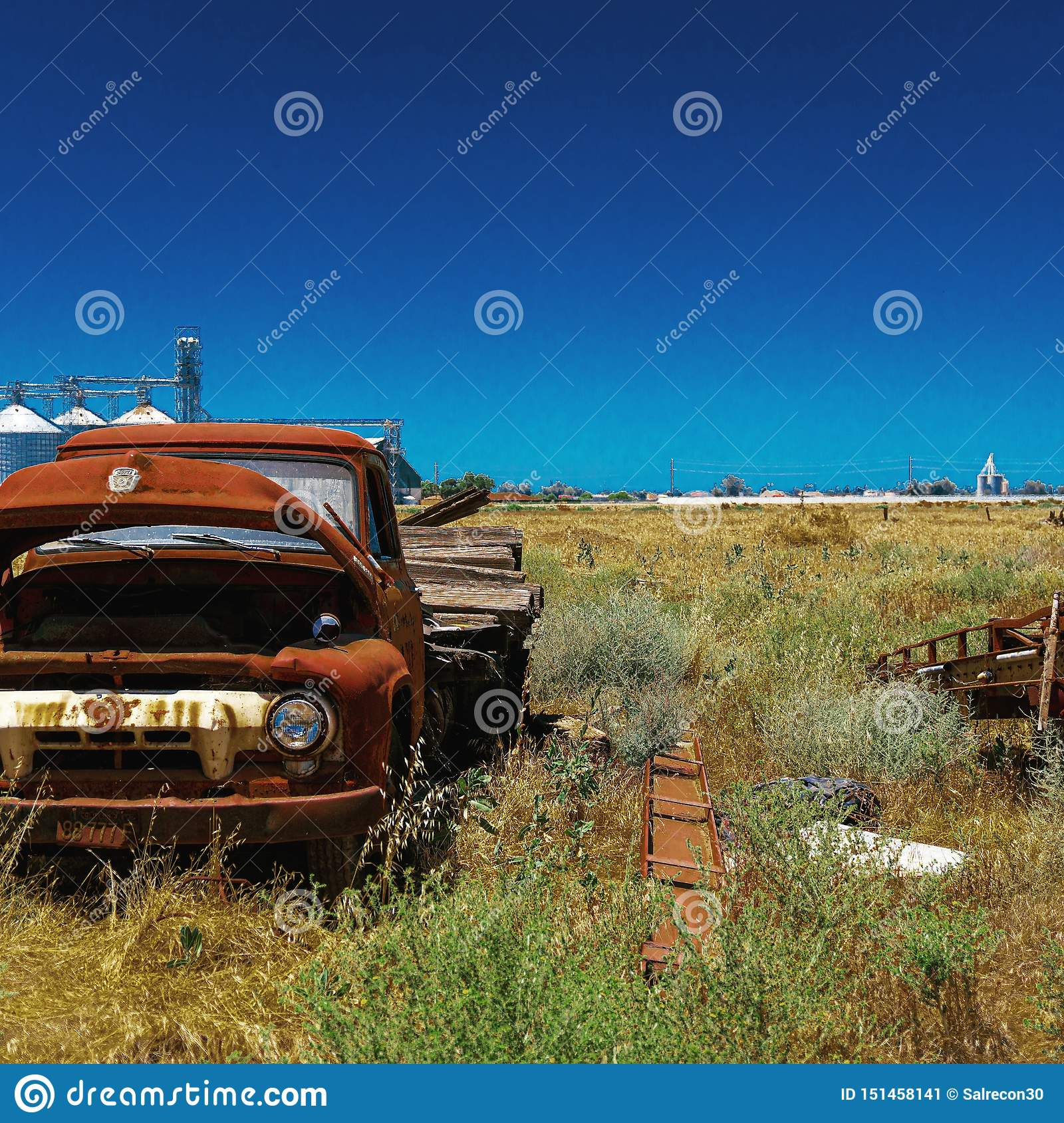 Abandoned old ford truck on farm by a factory