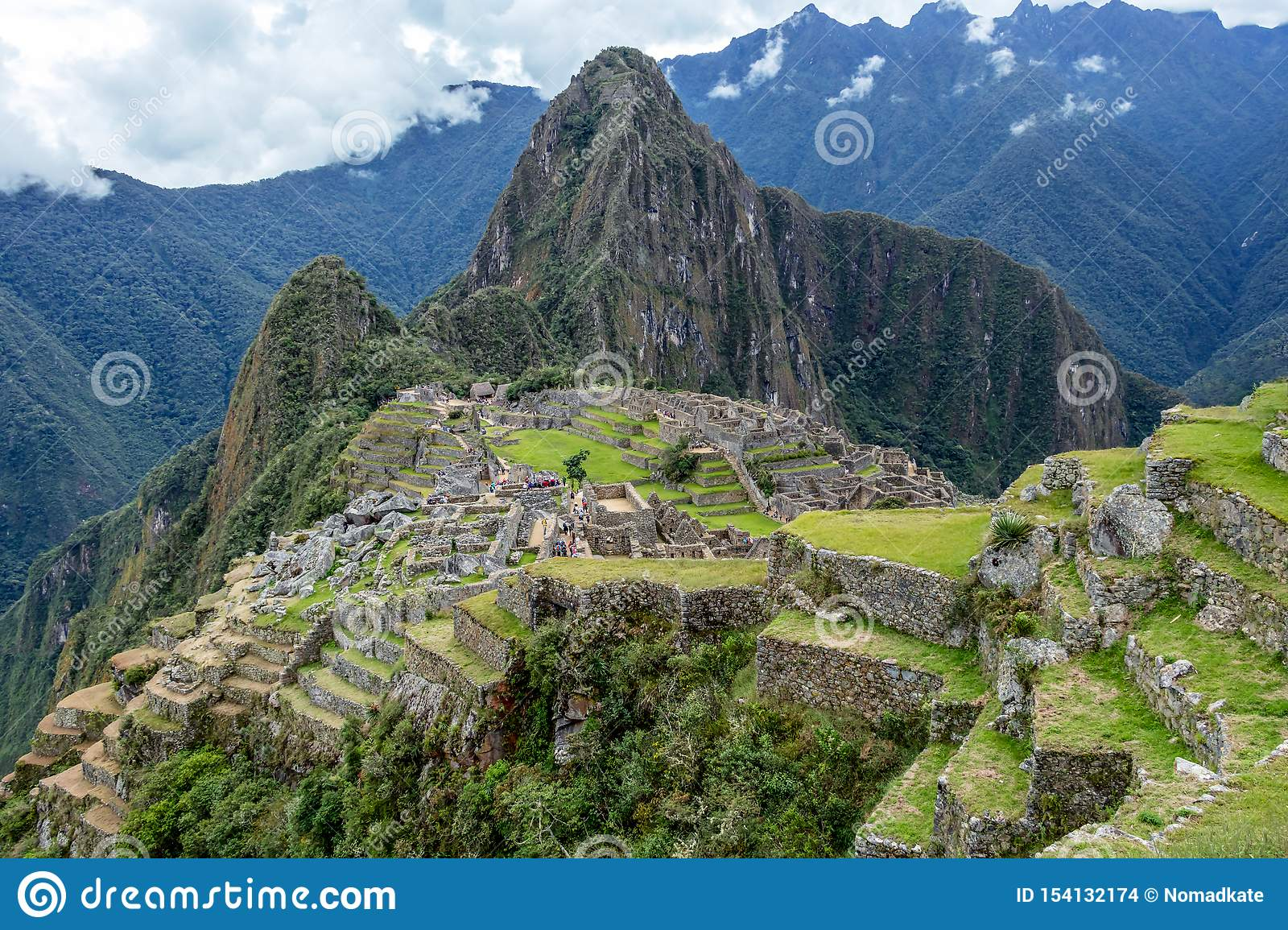 Abandoned ruins of Machu Picchu Incan citadel, the maze of terraces and walls rising out of the thick undergrowth, Peru