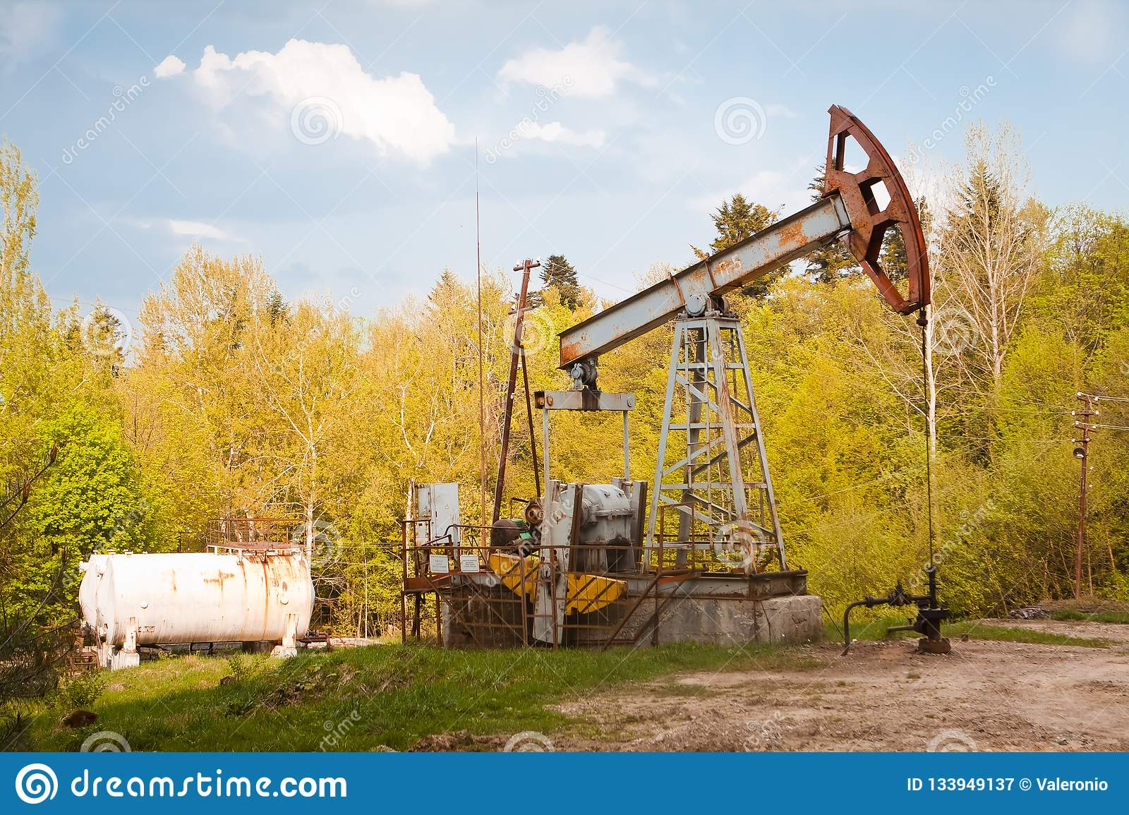 Abandoned rusty broken oil pump and pipeline equipment in forest, oil extraction rig, spring evening