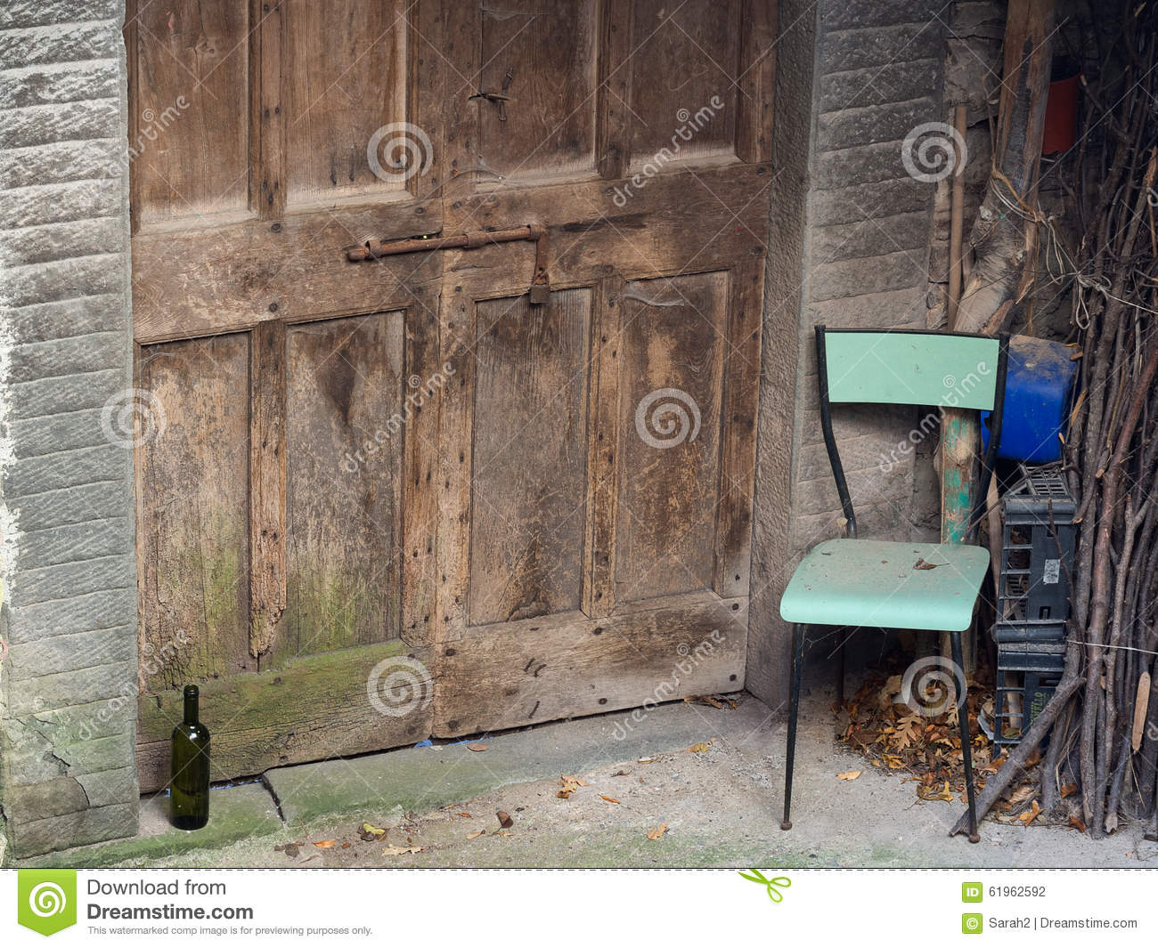Abandoned village doorway with chair and wine bottle. Poignant.