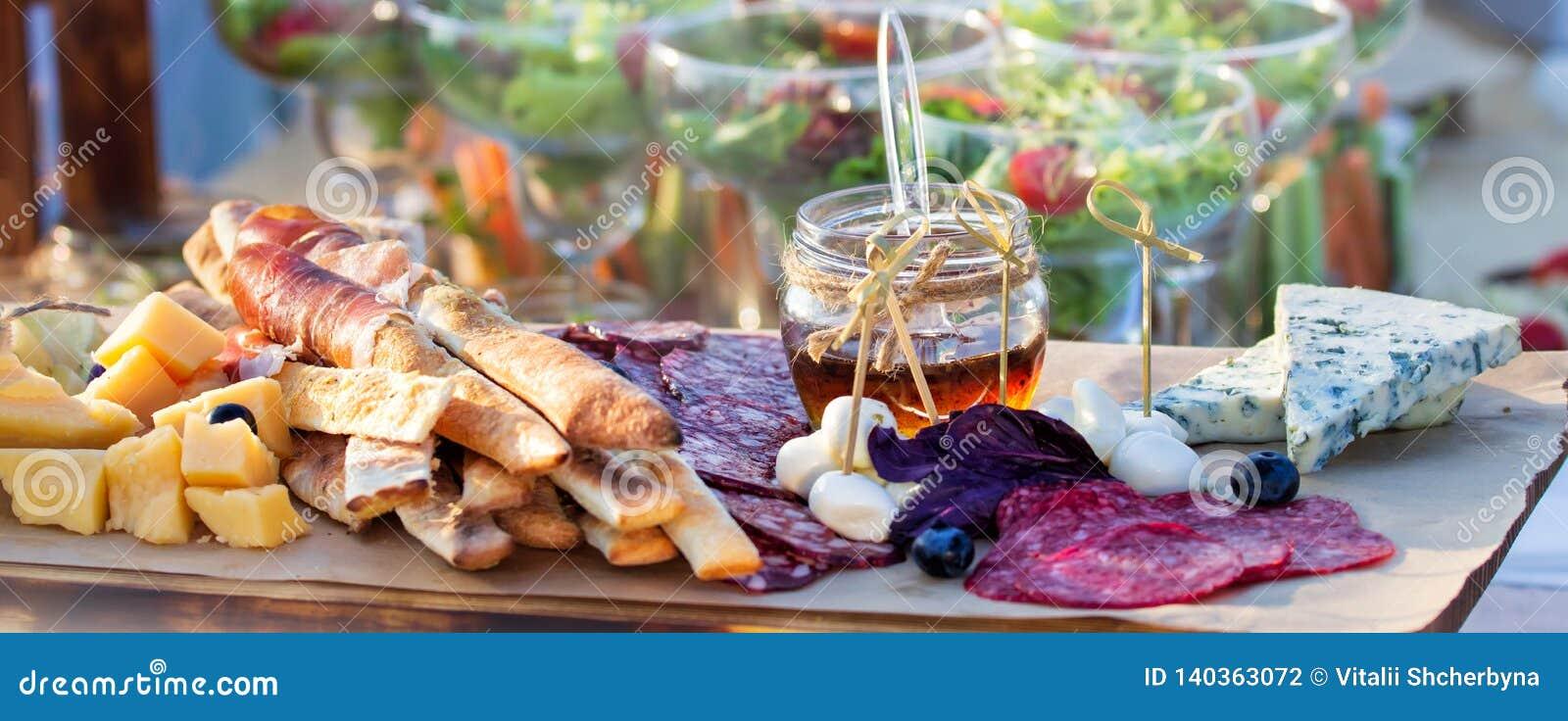 Abastecimiento de la comida fría de la comida que cena comiendo el partido que comparte concepto La gente agrupa la comida de aba