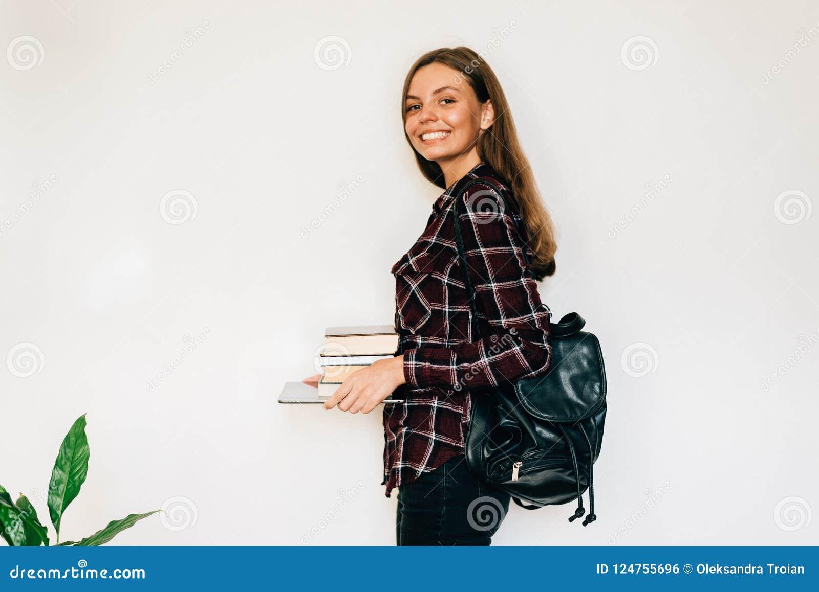 Abbastanza teenager dori lo studente della scuola o dell istituto universitario con la pila di istruzione dei libri