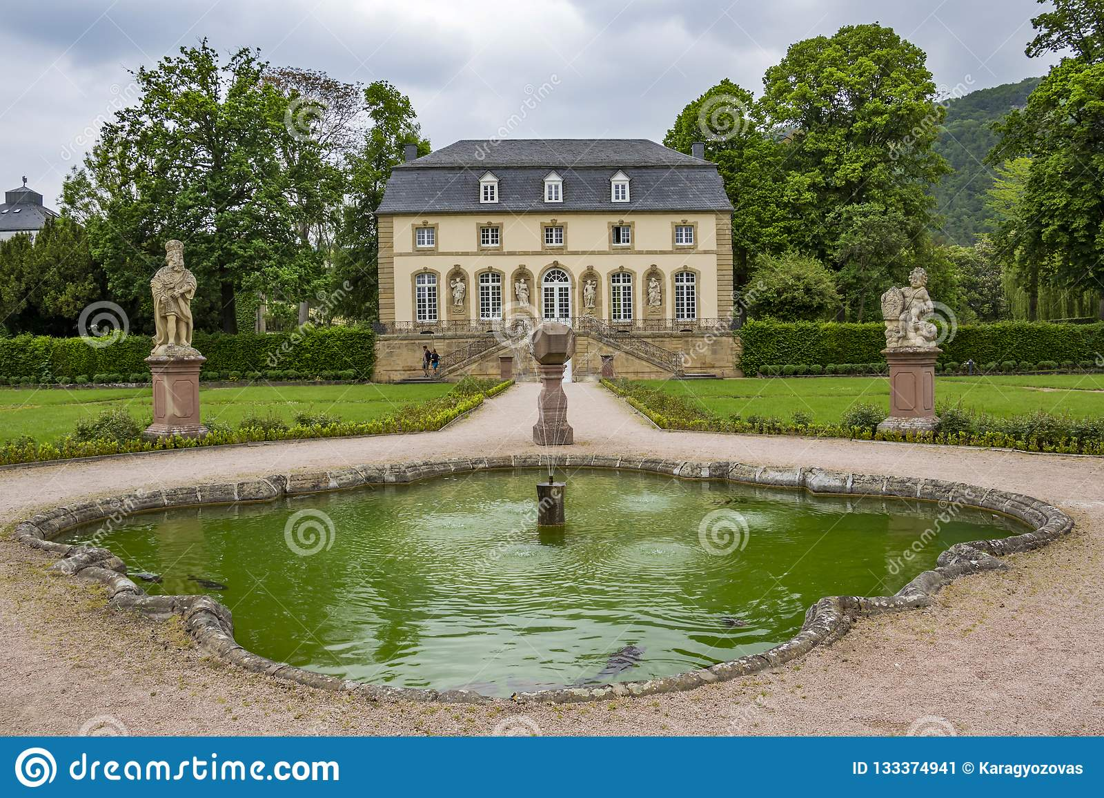 The abbey garden in Echternach, Luxembourg with a fountain and the building of the Orangery on an overcast May day