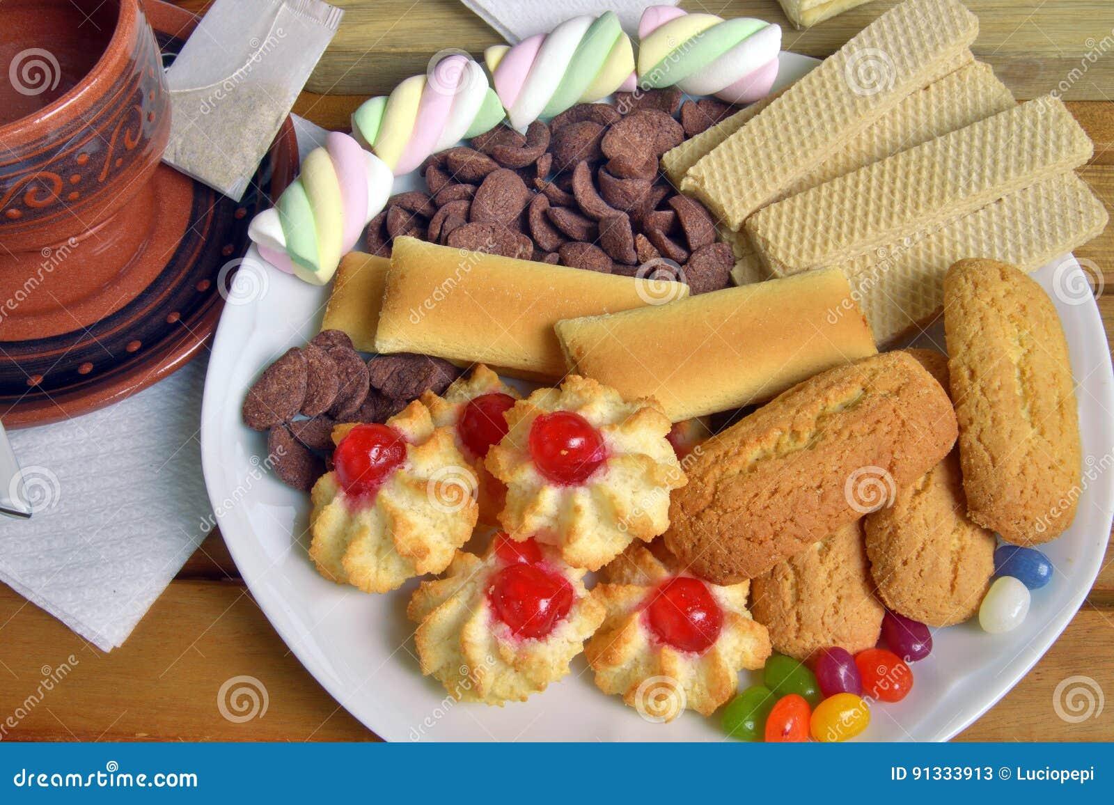Abbia prima colazione a casa con tè ed i biscotti