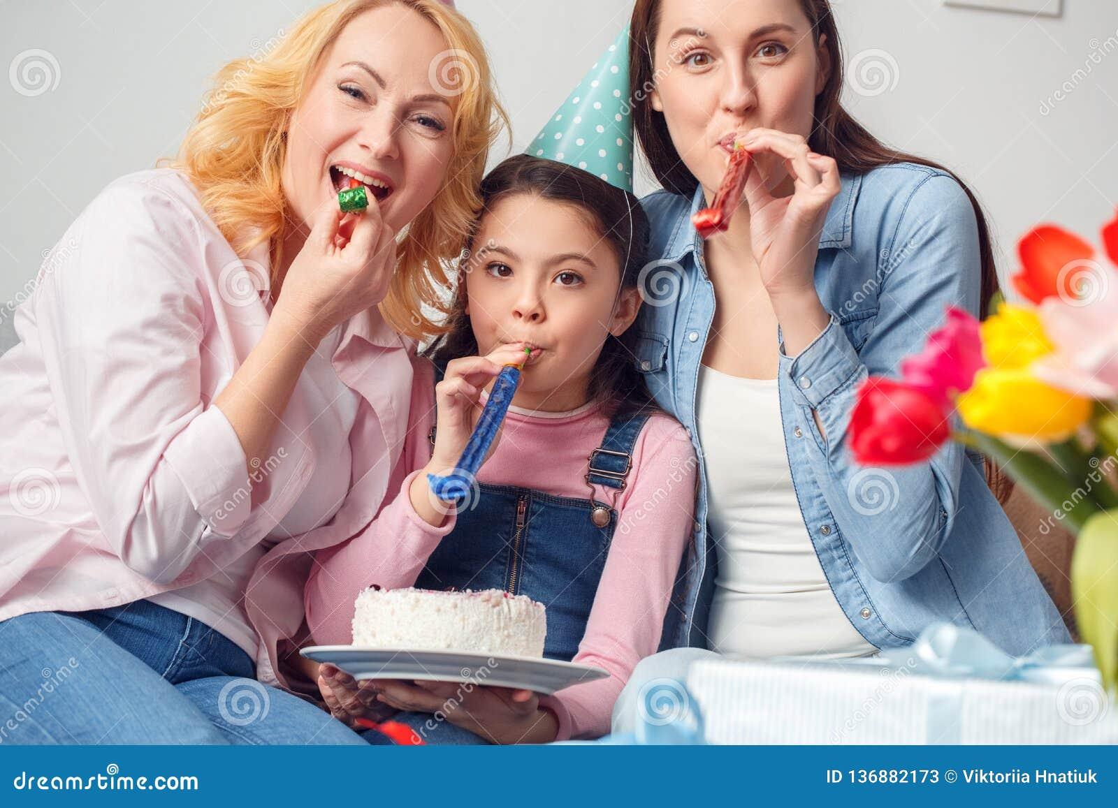 Abbracciare di seduta di compleanno della madre e della figlia della nonna insieme a casa giudicando i corni di salto del dolce f