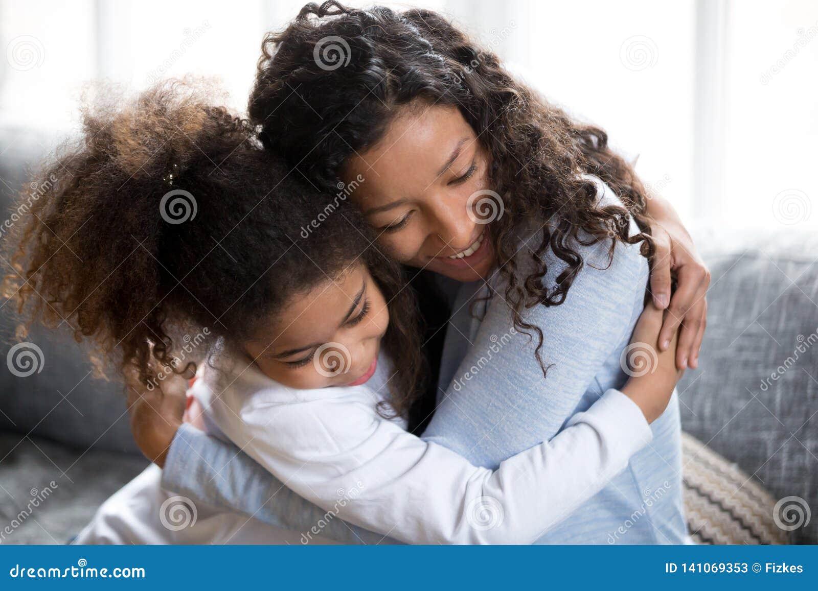 Abbraccio afroamericano felice della figlia e della mamma che fa pace