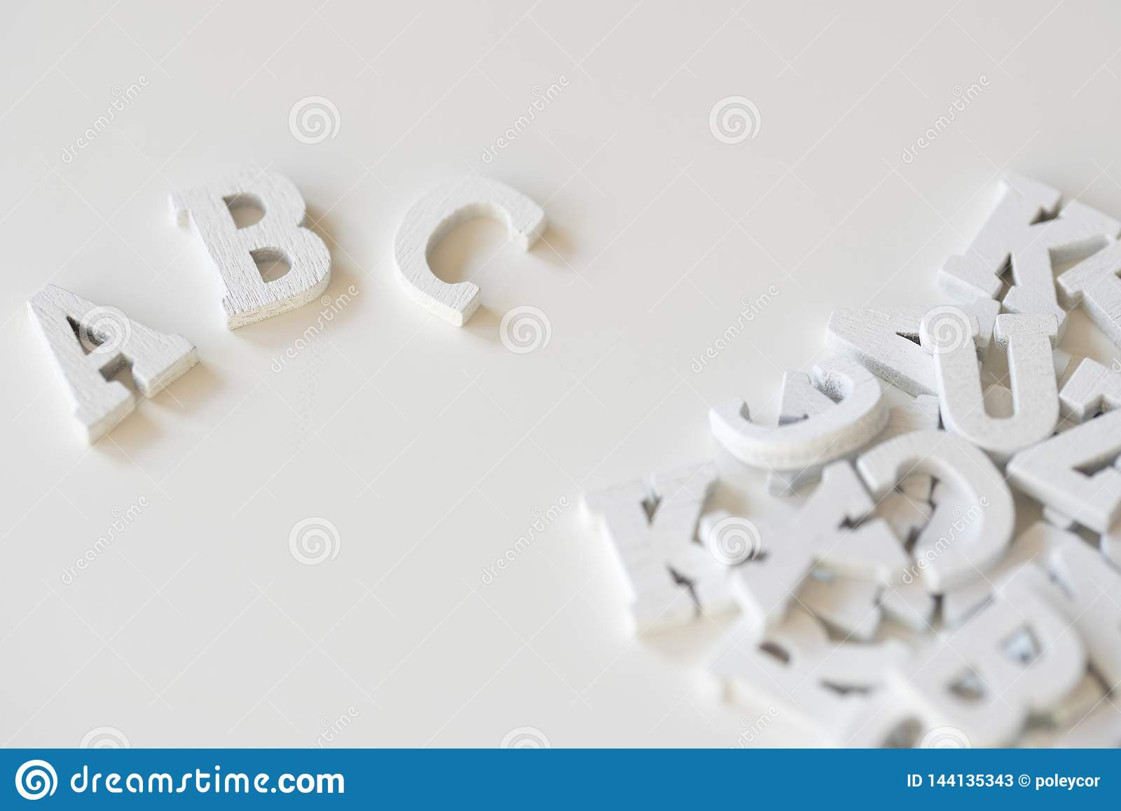 ABC escrito con las letras de madera blancas, contra el fondo blanco