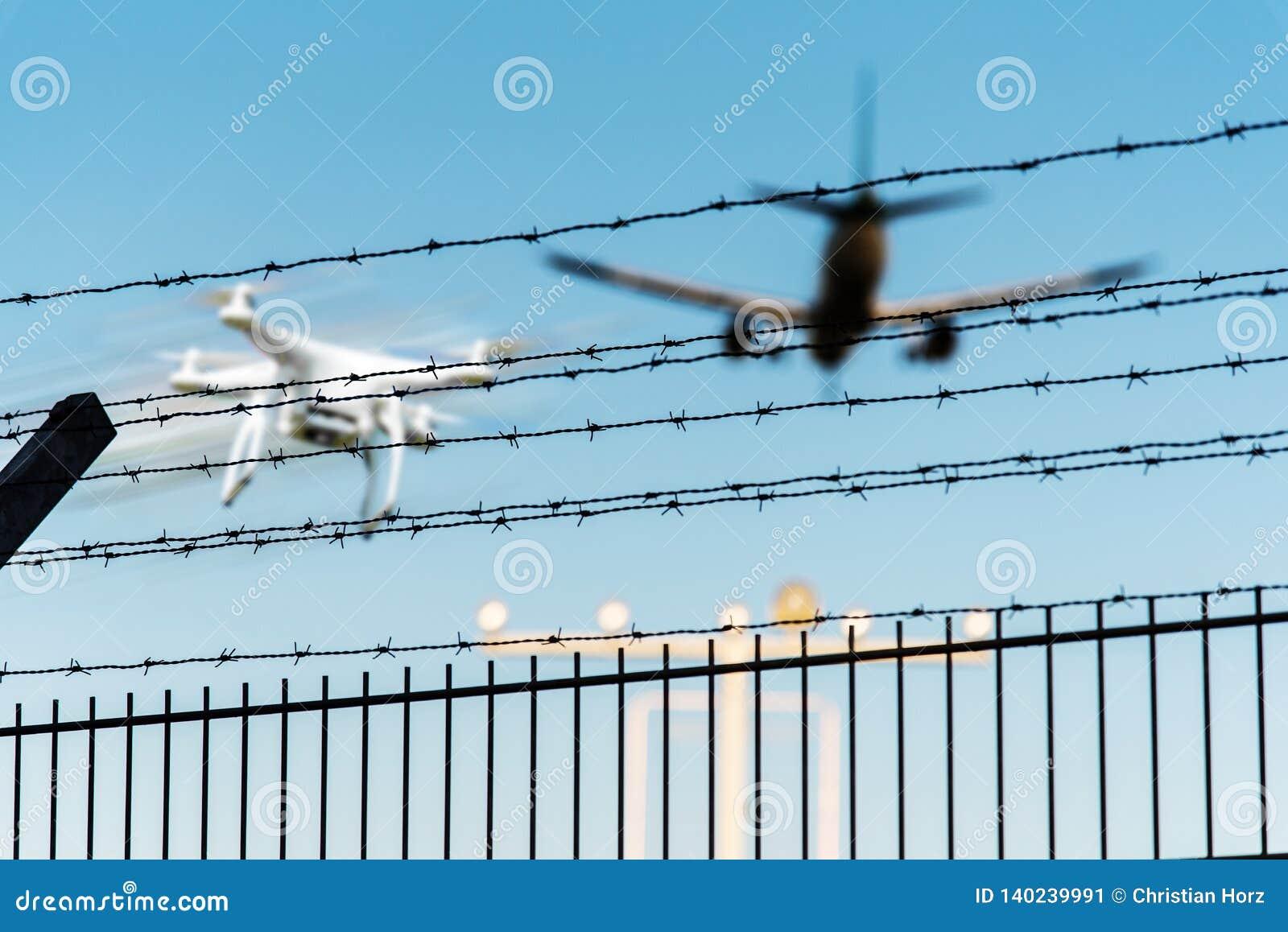 Abejón de Quadcopter en vuelo cerca de la pista inminente del aeropuerto del aeroplano