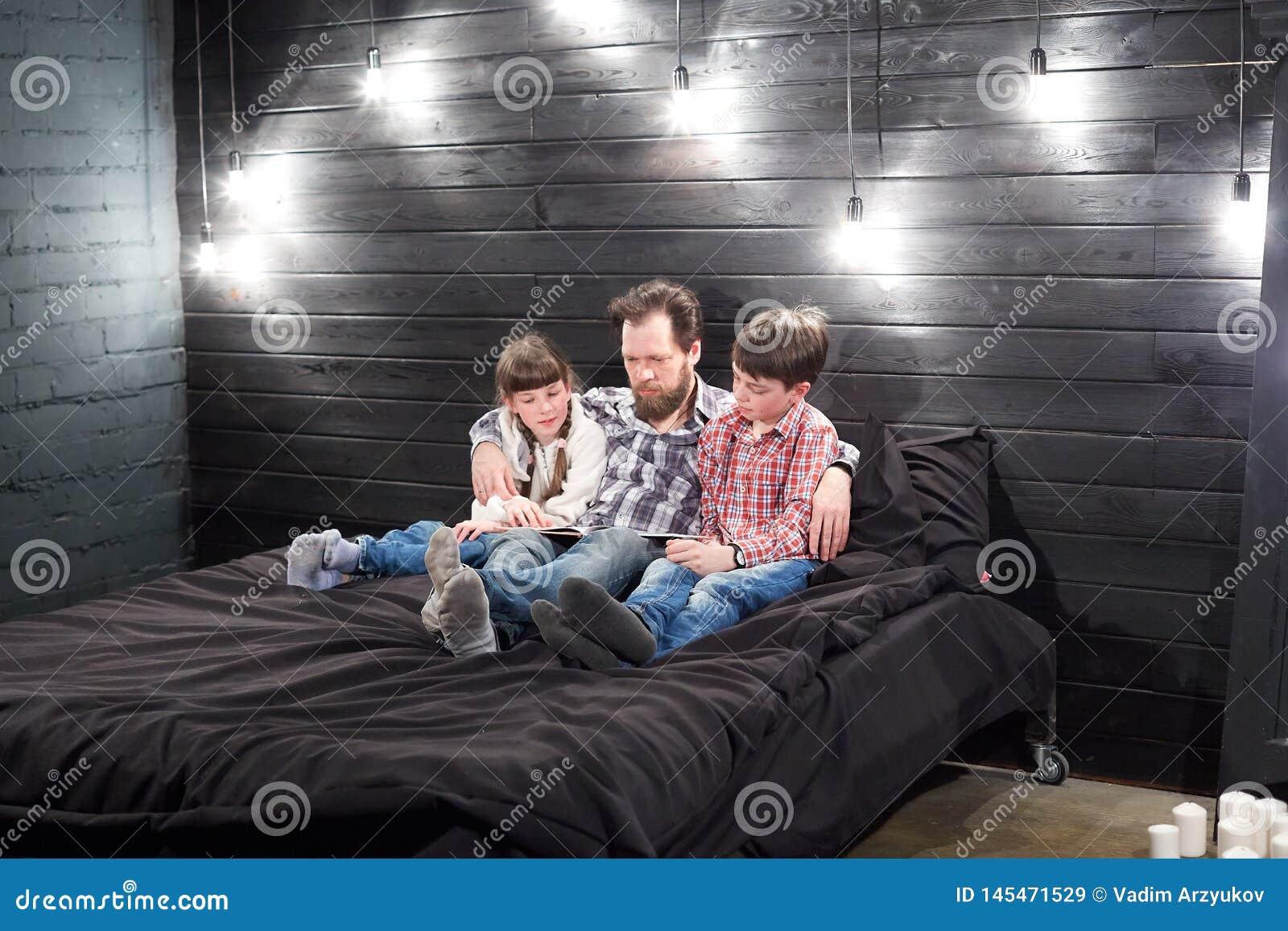 Abendfamilienlesung Vater liest Kinder ein Buch, bevor er schlafen geht