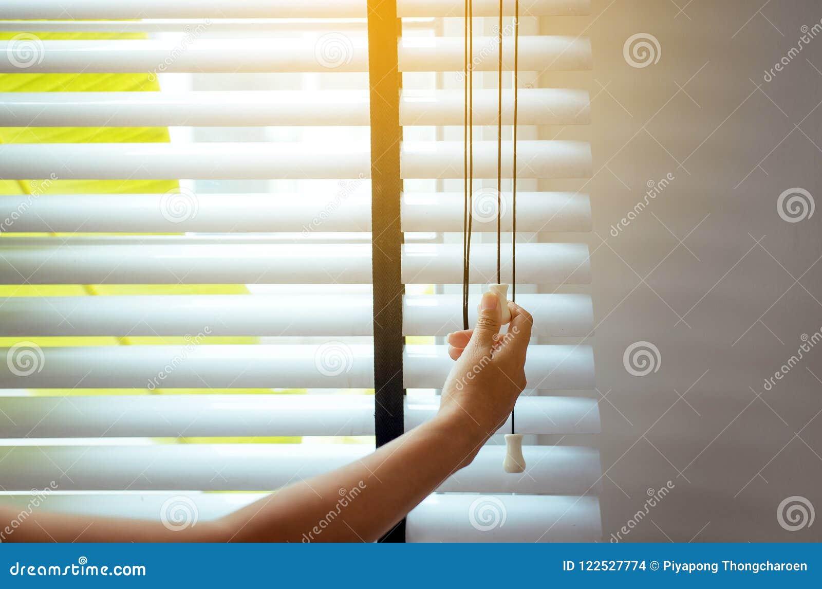 A abertura da mulher da mão cega a janela na sala de visitas para obter a luz solar