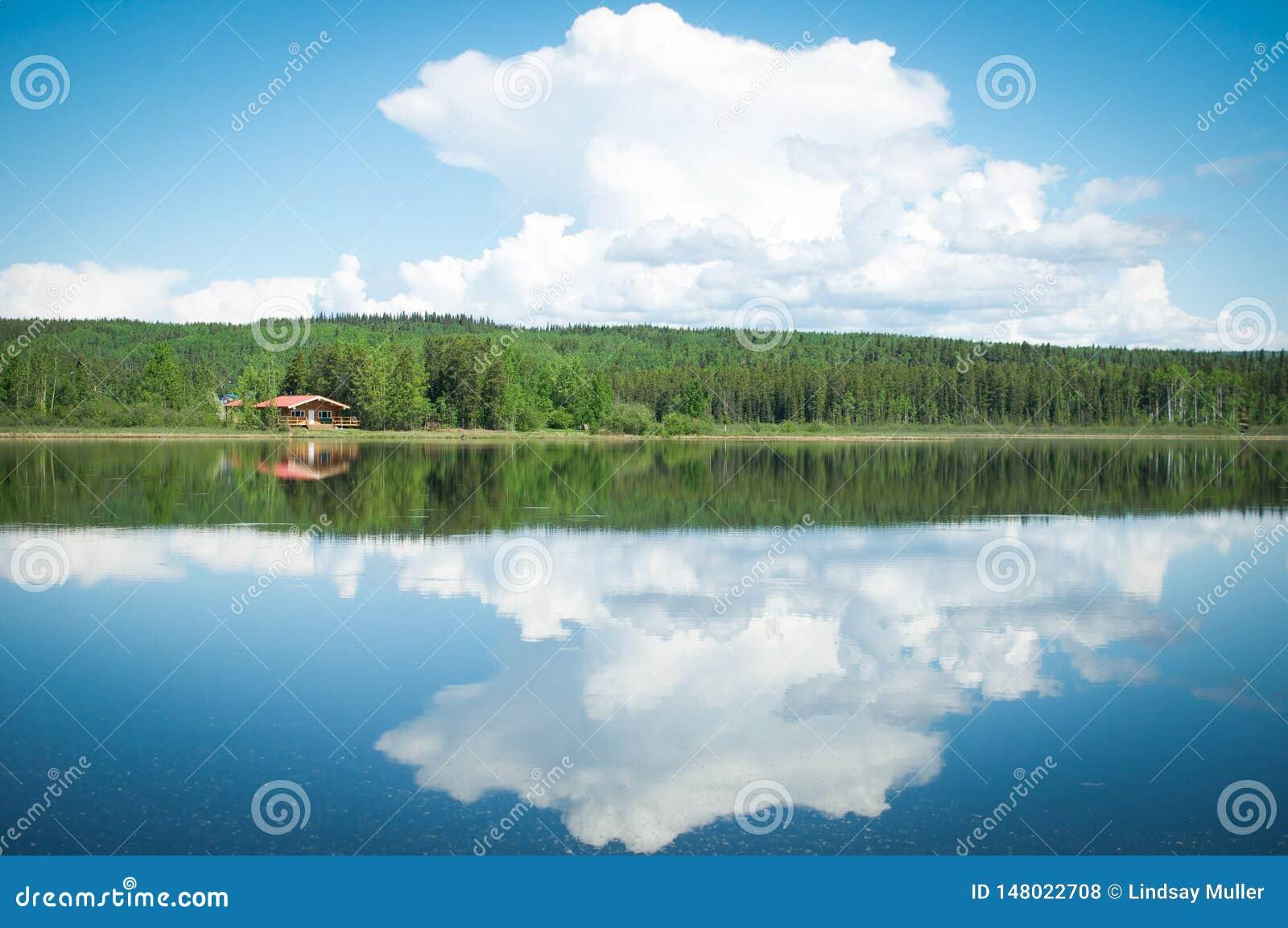 Abgeschlossene Kabine auf einem reflektierenden See in Yukon, Kanada