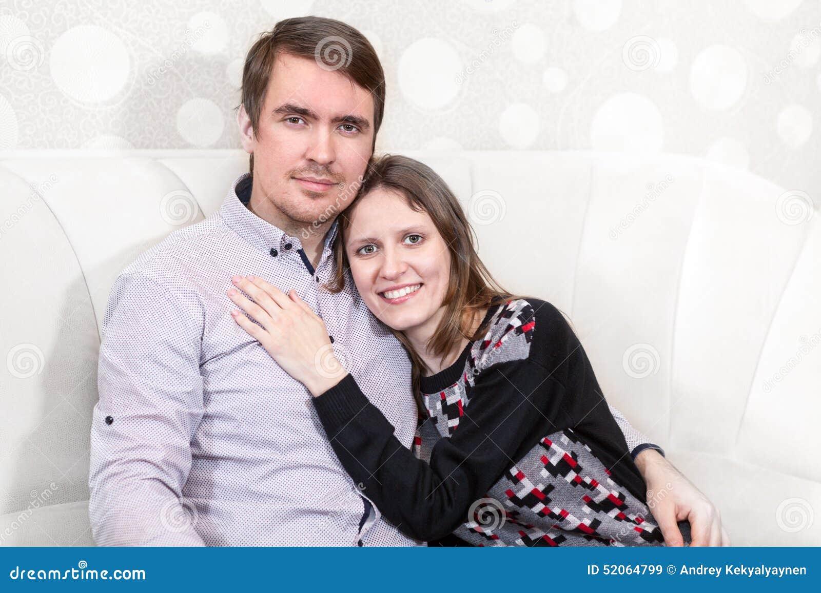 Abraçando os pares loving que sentam-se no sofá, jovens