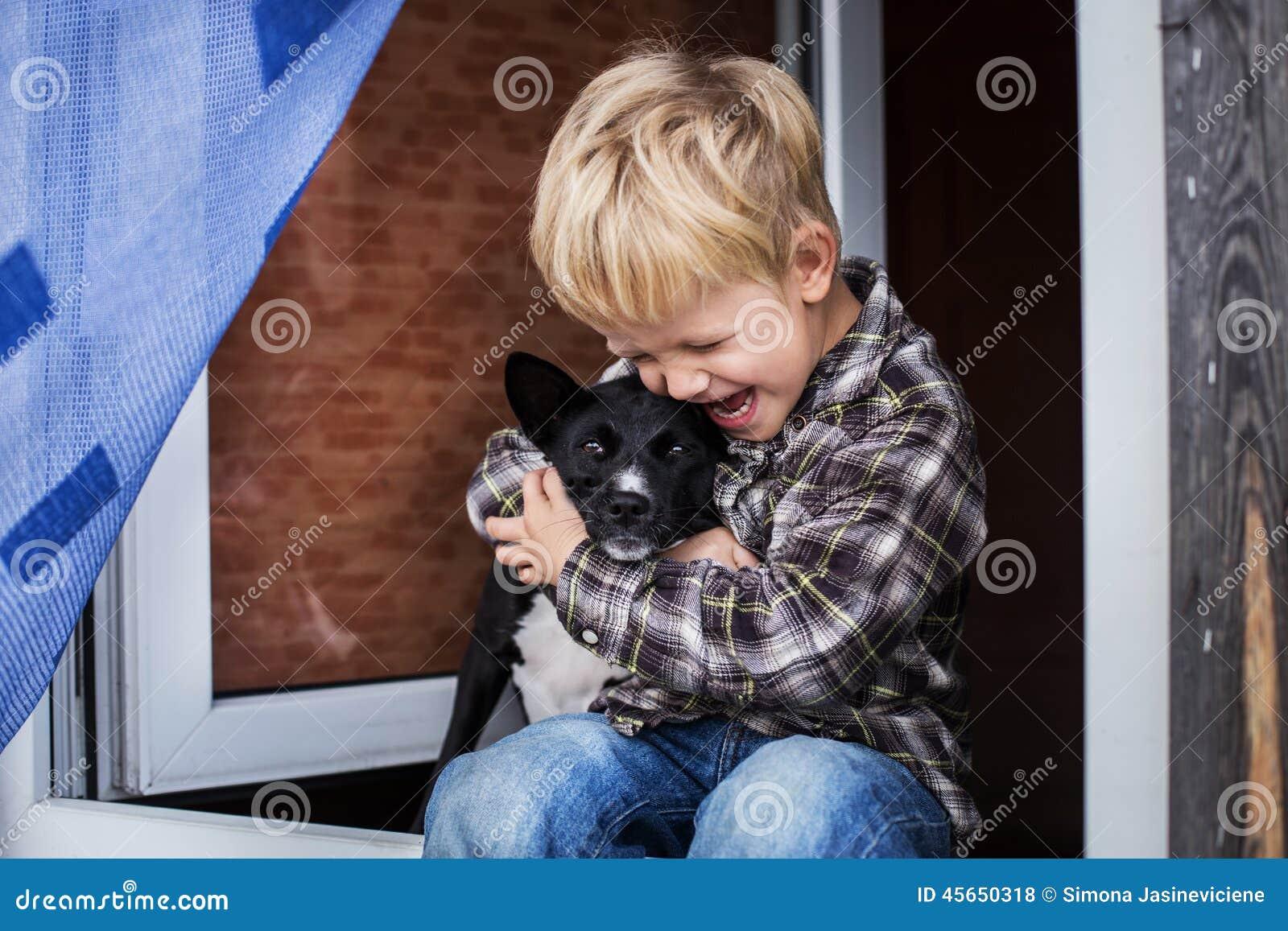 abraço louro bonito da criança seu cão amizade entre o ser humano e