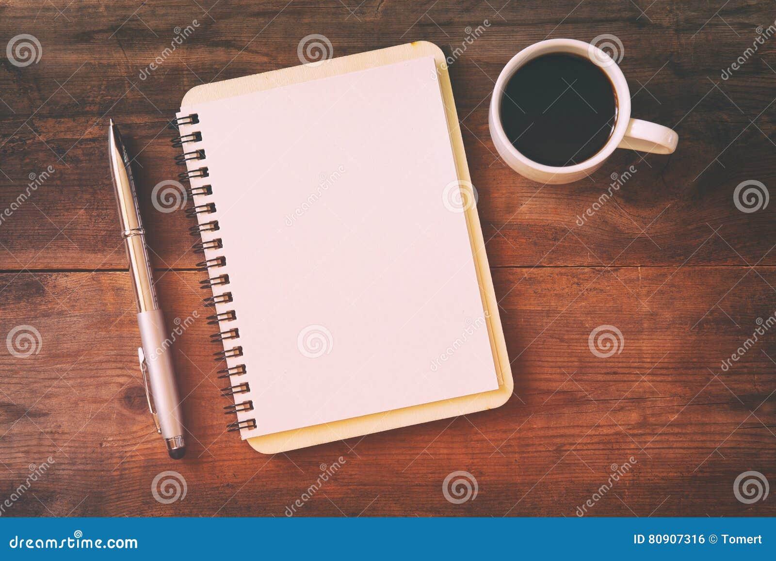 Abra el cuaderno con las páginas en blanco al lado de la taza de café
