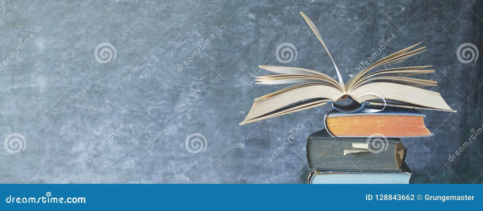 Abra el libro en una pila de libros viejos, pizarra