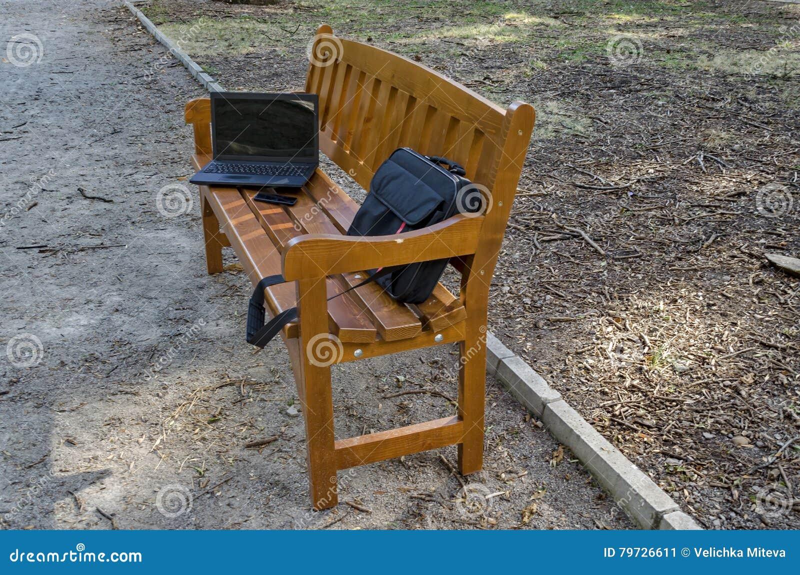 Abra el ordenador portátil, el bolso y el teléfono en banco de madera