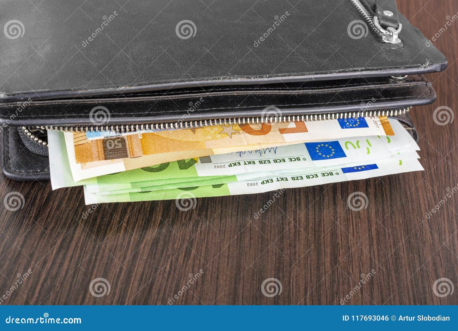 Abra la cartera con efectivo euro 10 20 50 100 en un fondo de madera Cartera del ` s de los hombres con euro del efectivo