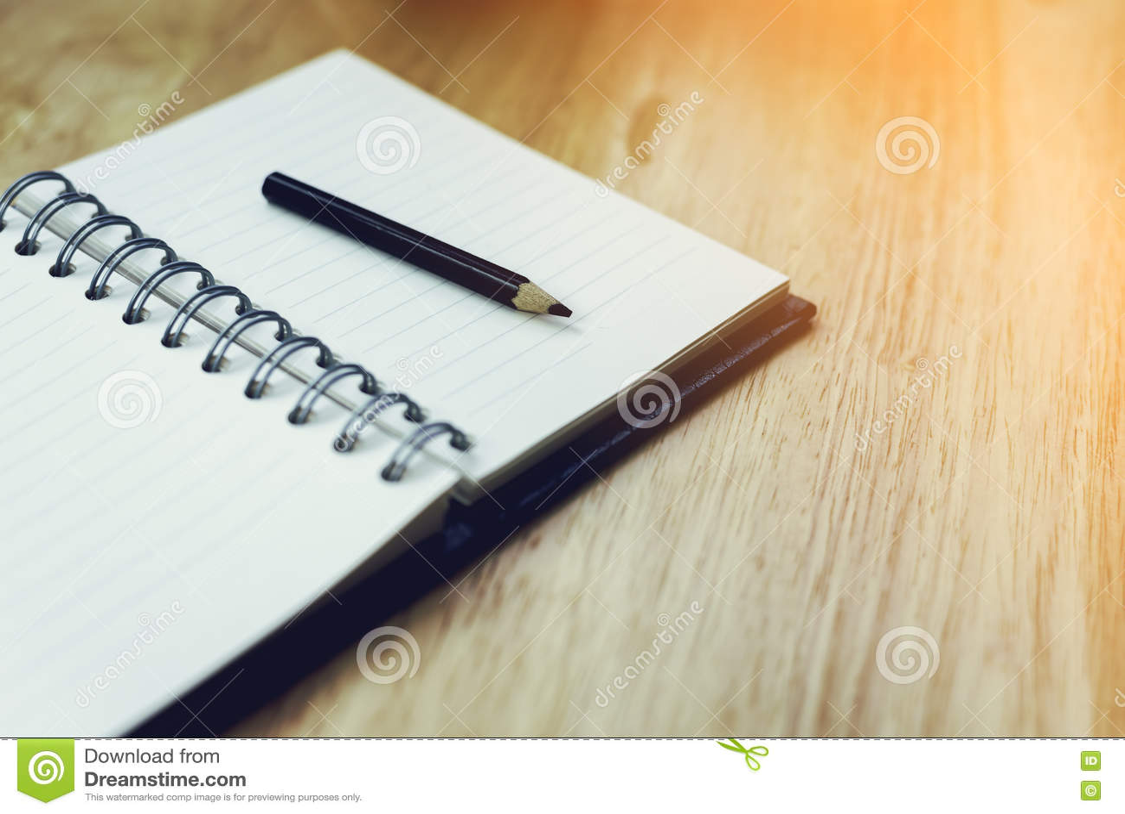 Abra o caderno com lápis e o despertador antiquado na madeira