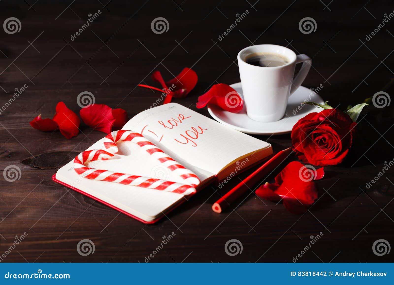 Abra O Caderno E Uma Rosa Vermelha Em Um Fundo Preto Foto De Stock