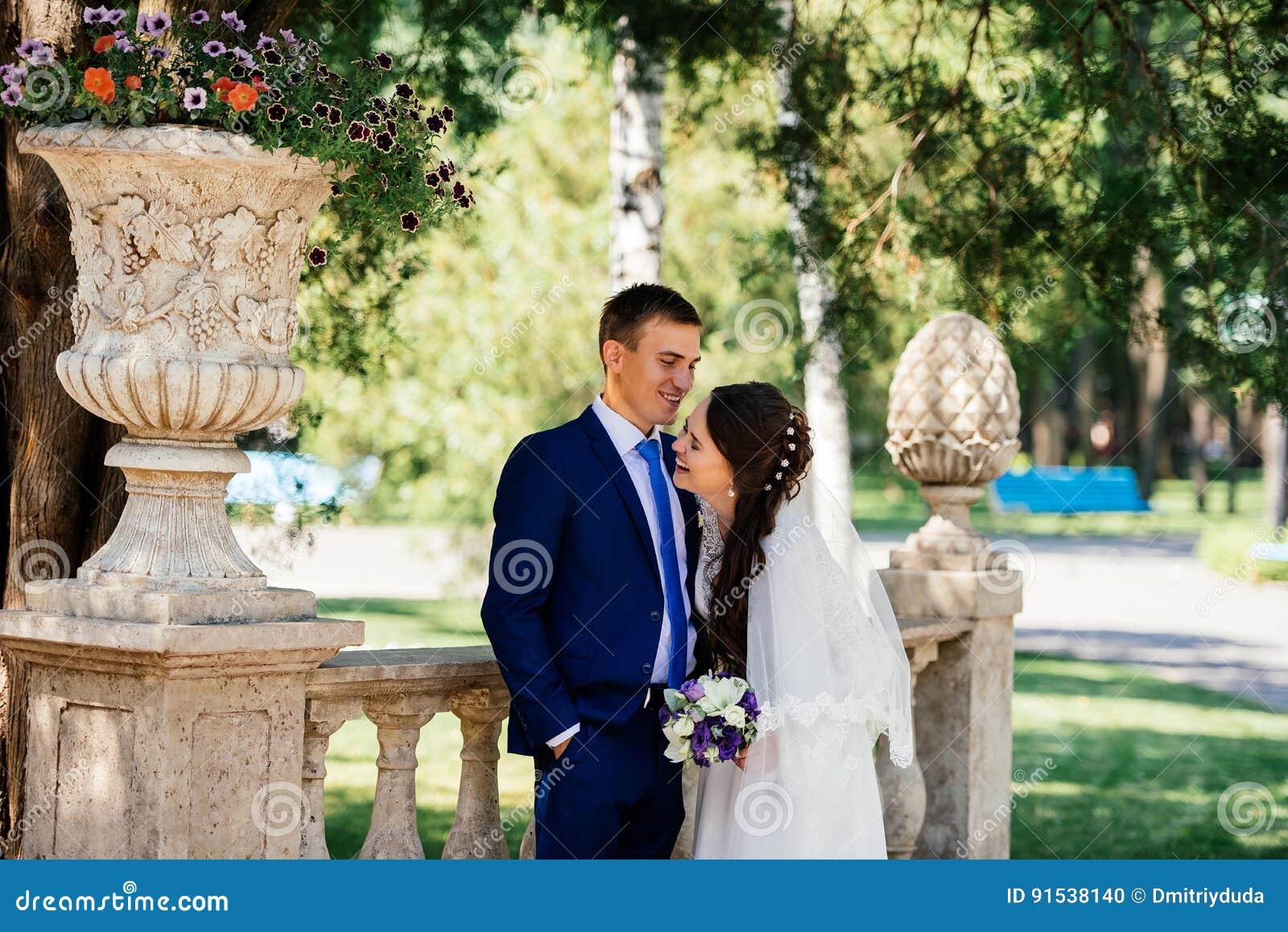 Abrazos sonrientes hermosos de novia y del novio de Yong en el parque la novia abraza al novio Pares en amor en el día de boda