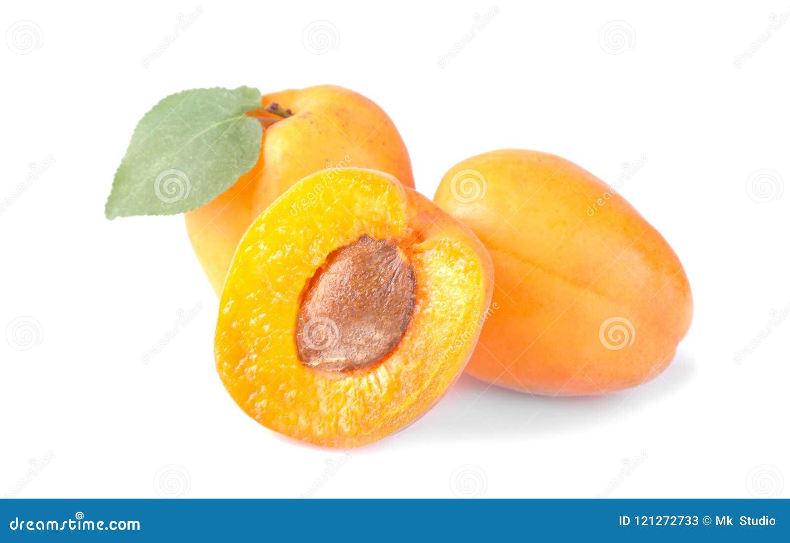 Abricots frais et une moitié d abricot avec une feuille sur un fond blanc d isolement