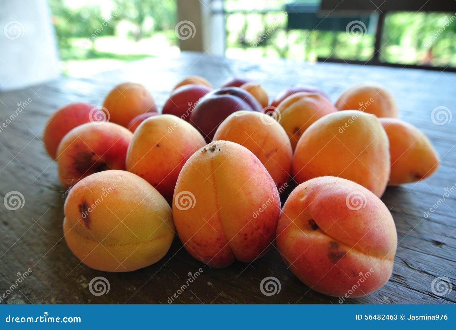 Abricots oranges mûrs sur la table en bois rustique, un jour ensoleillé d été