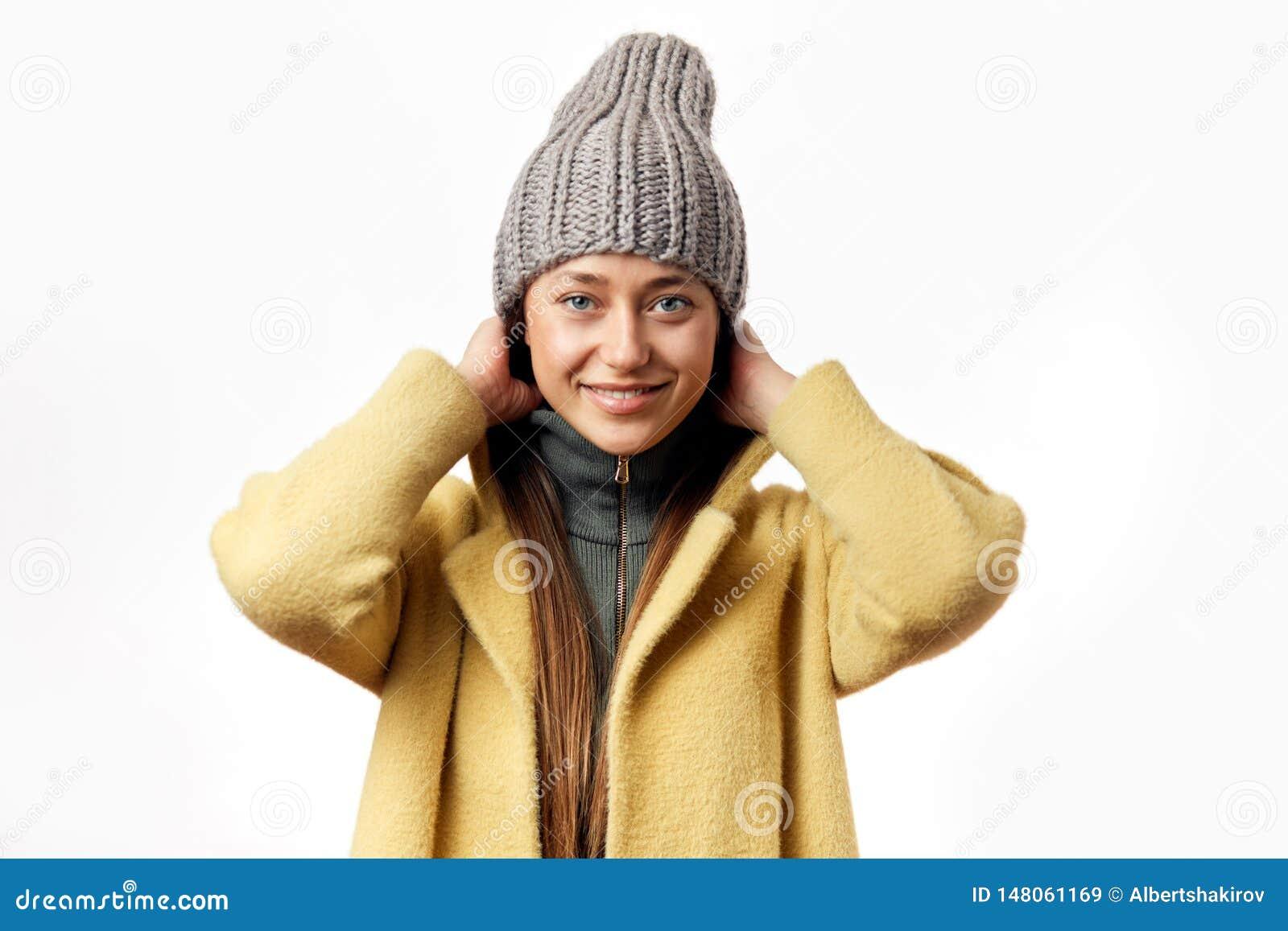 Abrigo de invierno que lleva de la mujer joven aislado sobre el fondo blanco