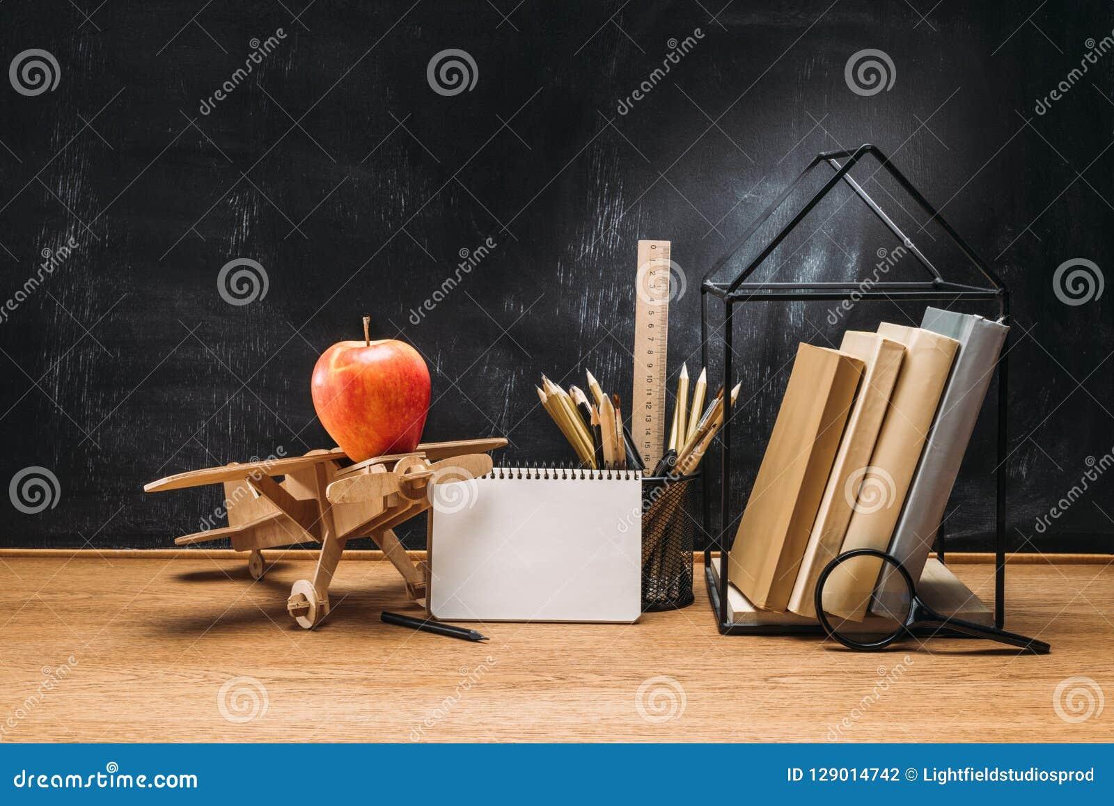 Abschluss herauf Ansicht des Apfels auf flachen Notizbuchbüchern und -bleistiften des hölzernen Spielzeugs auf Tischplatte mit le