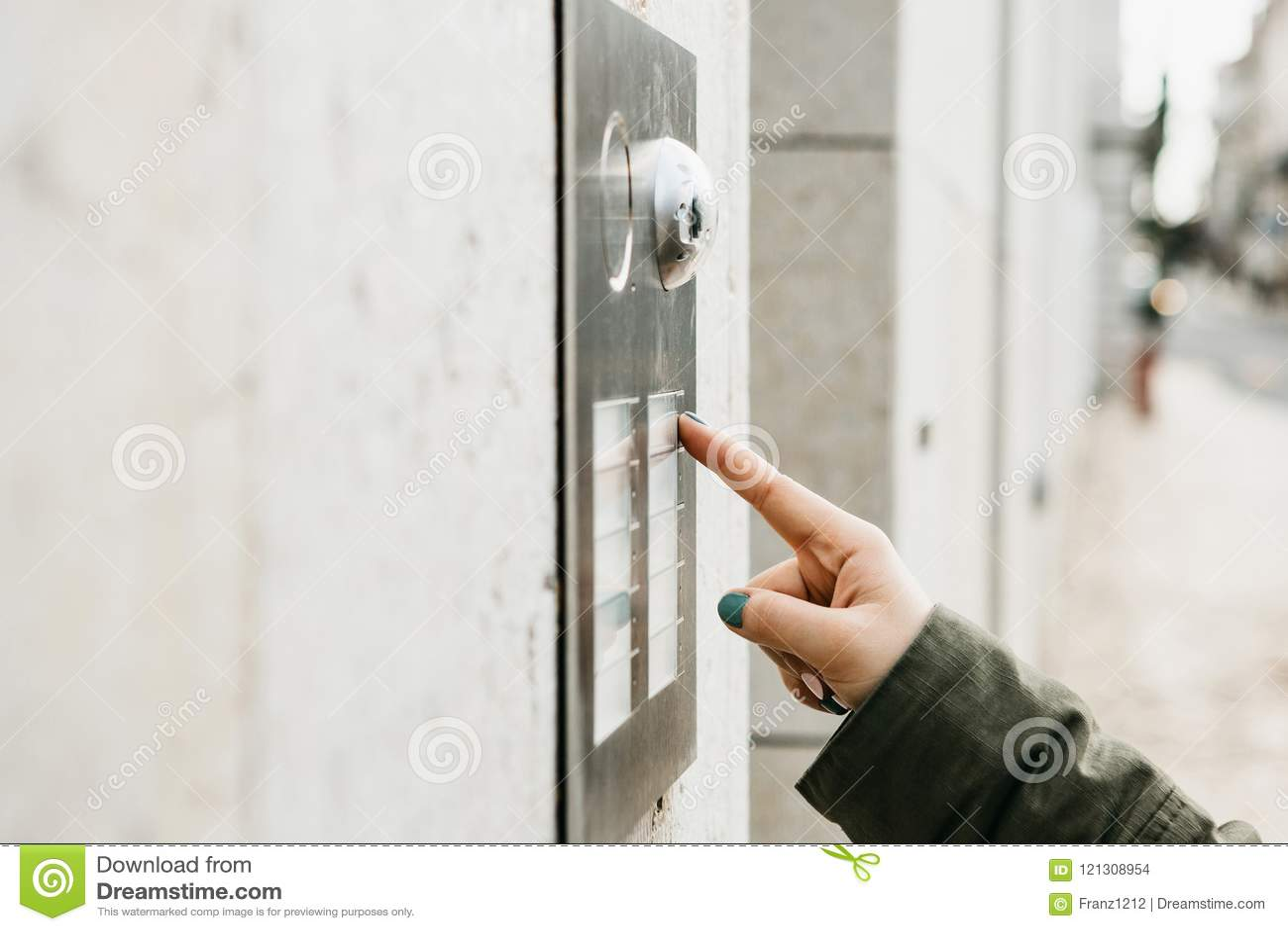 Abschluss herauf die weibliche Hand drückt den doorphone Knopf Das Mädchen nennt die Wechselsprechanlage