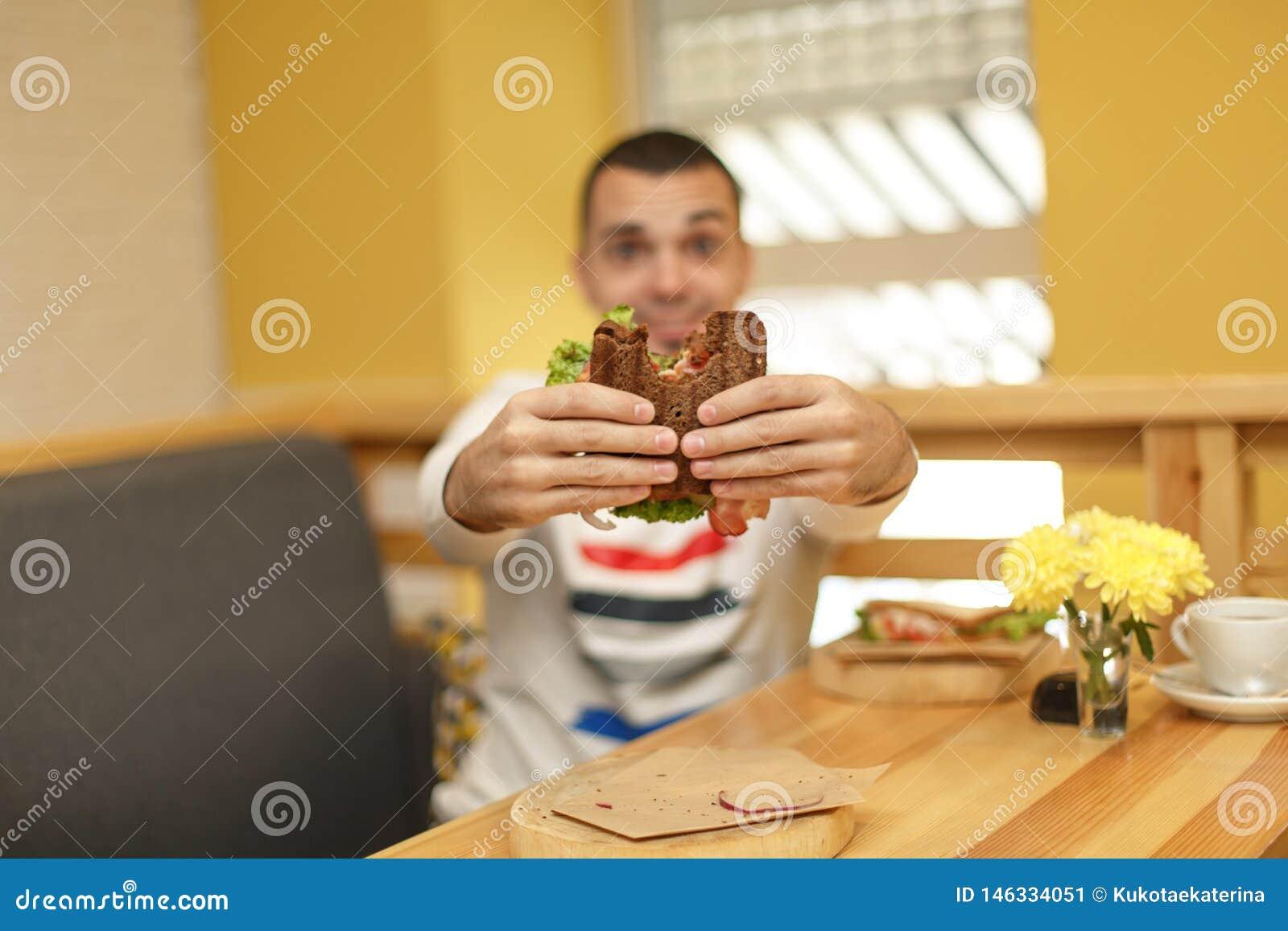 Abschluss herauf lustiges unscharfes protrait des gebissenen Sandwiches des jungen Mannes Griff durch seine zwei H?nde Sandwich i
