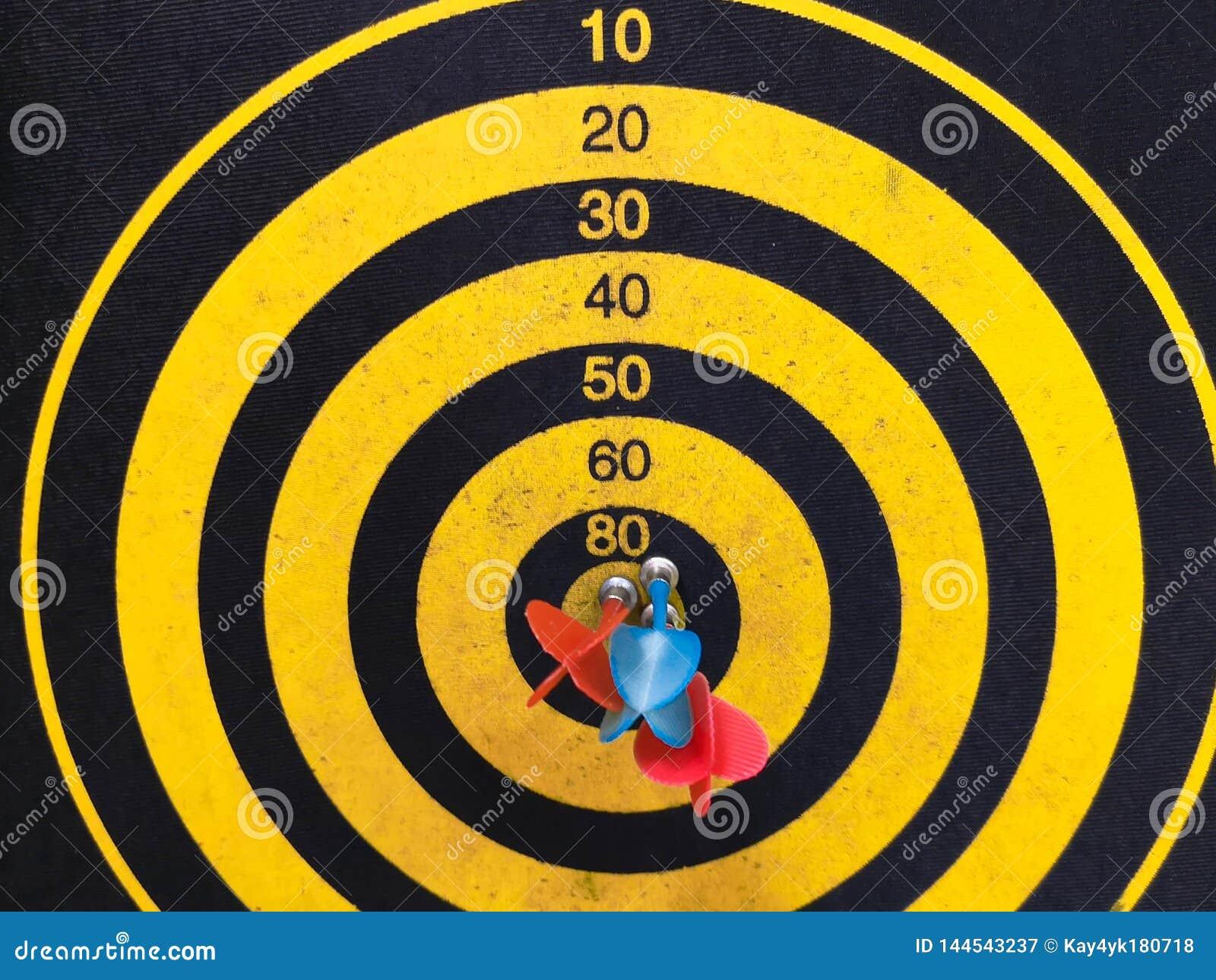 Abschluss schoss oben von einer Dartscheibe Pfeilpfeil, der das Ziel auf einer Dartscheibe w?hrend des Spiels verfehlt Pfeilgelb