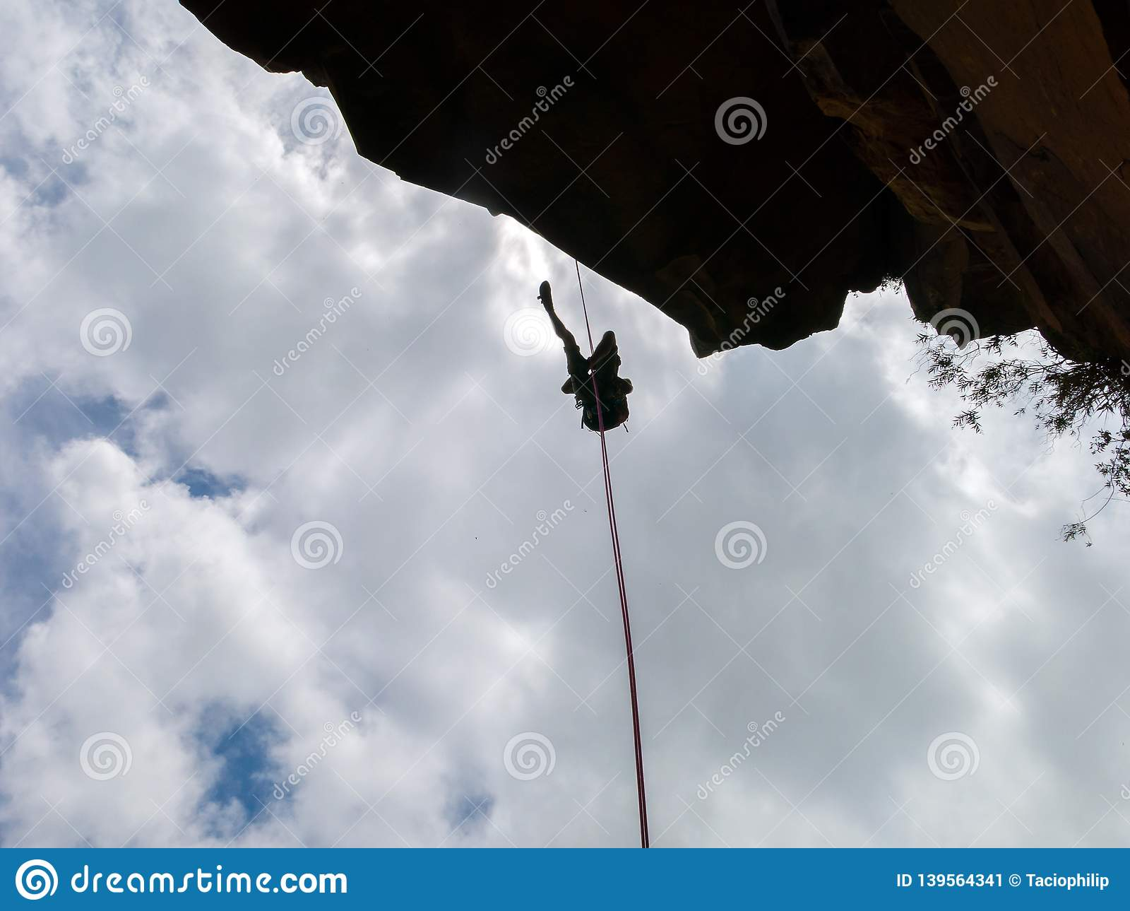 Abseiling a negative sanstone rock wall with blue sky on background - view from bellow