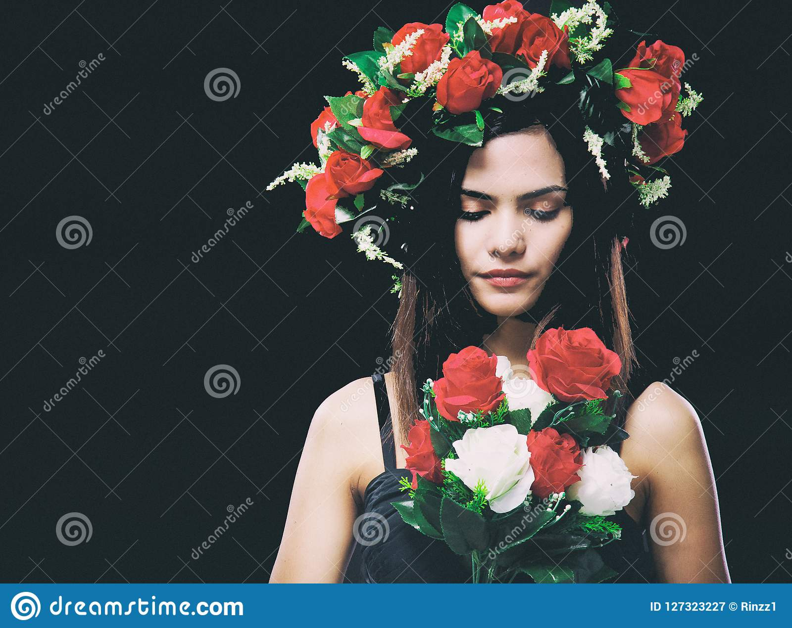 The abstract art design background of beauty lady is wearing rose crown,looking rose bouquet in hands,vintage and art tone