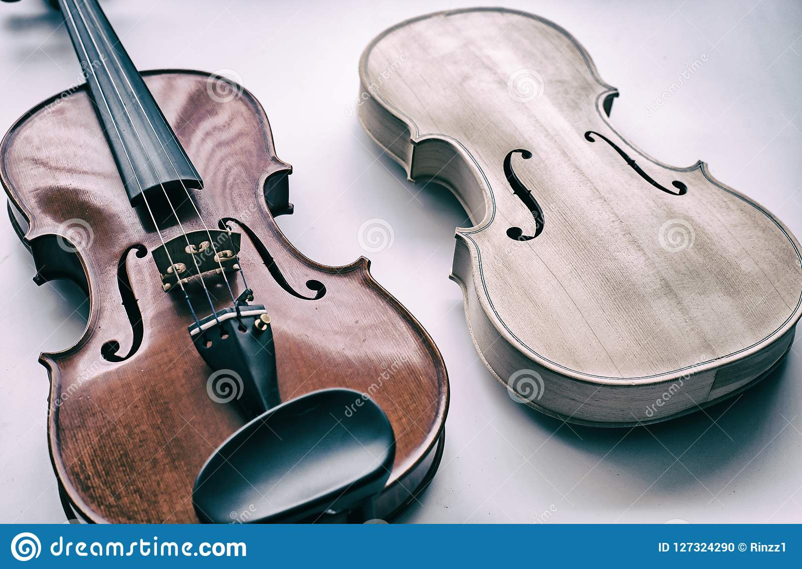 The abstract art design background of raw violin put beside completed violin