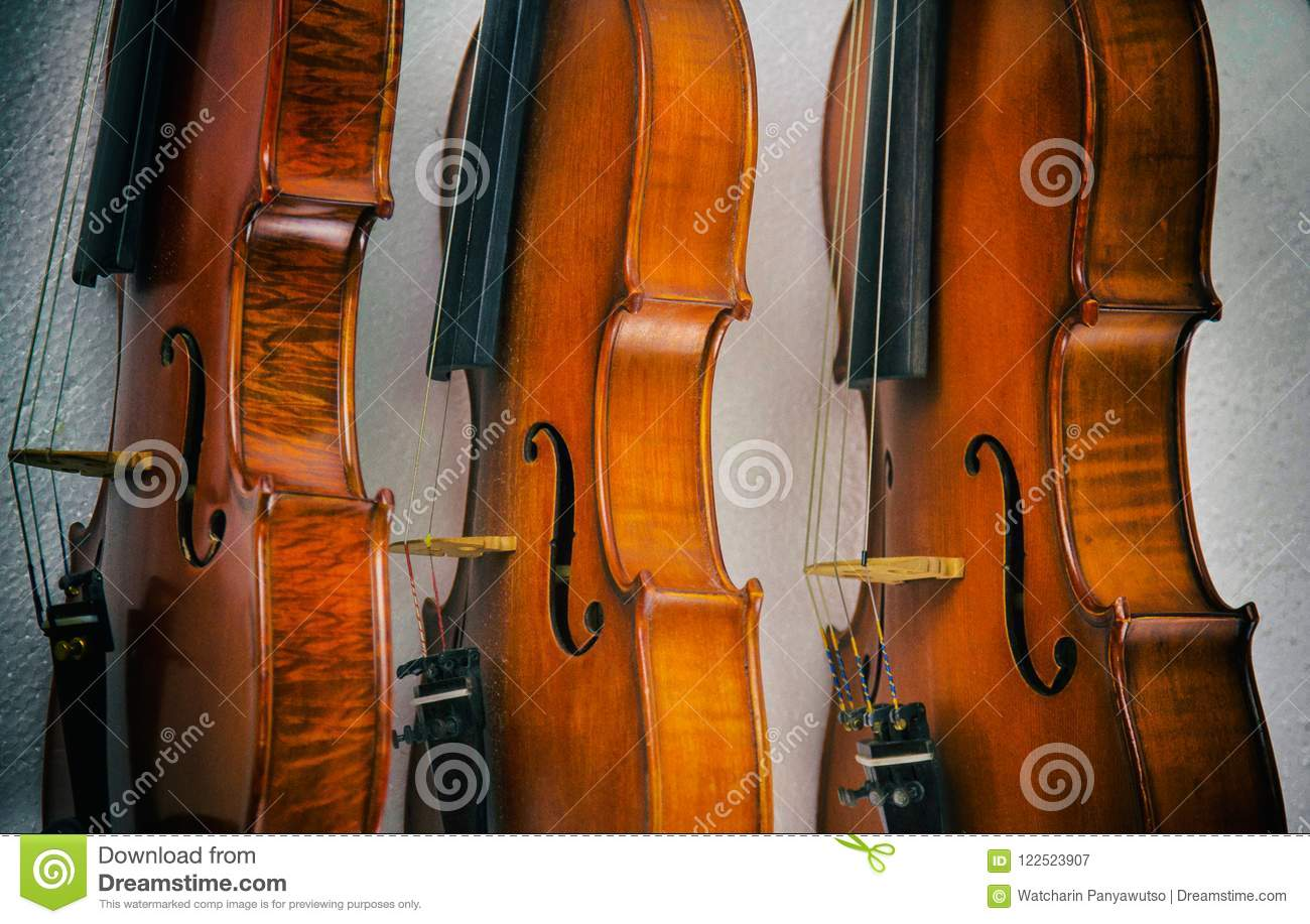 The abstract art design background of three violins stacked on background.show side of wood on violin,vintage and art style