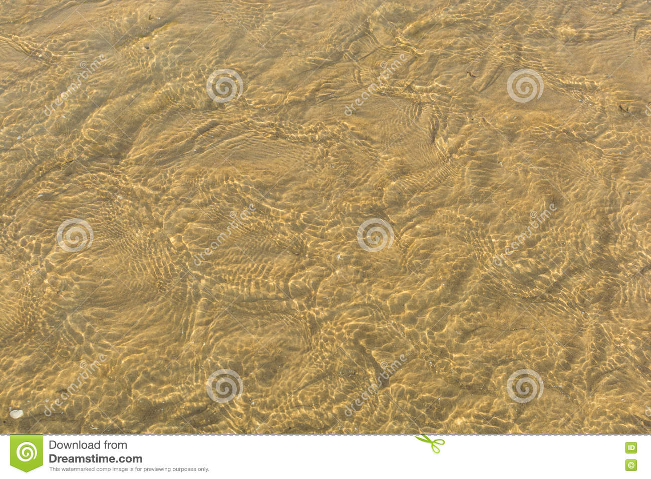 Abstract background of sand ripples under clear water at the beach