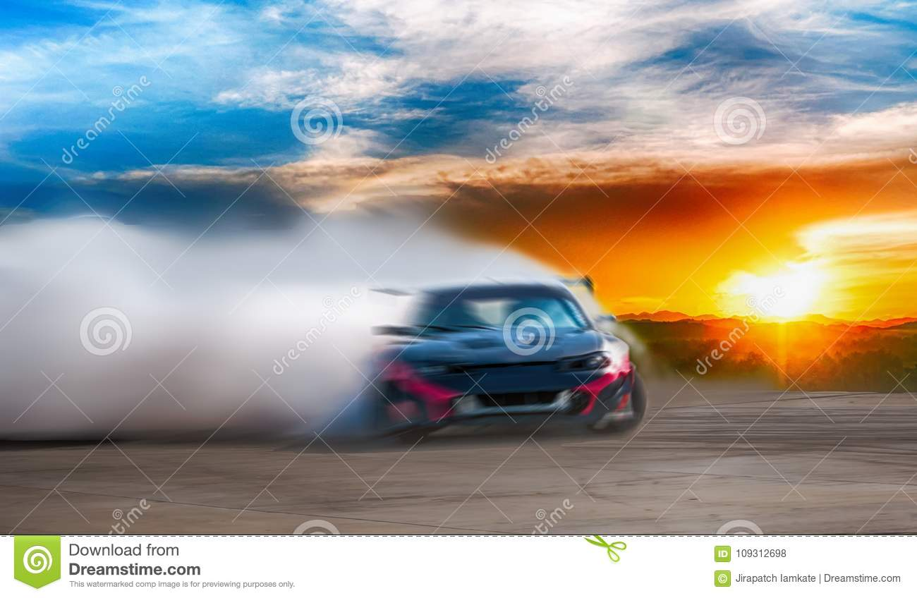 Abstract blurred drift car with smoke from burned tire at sunset