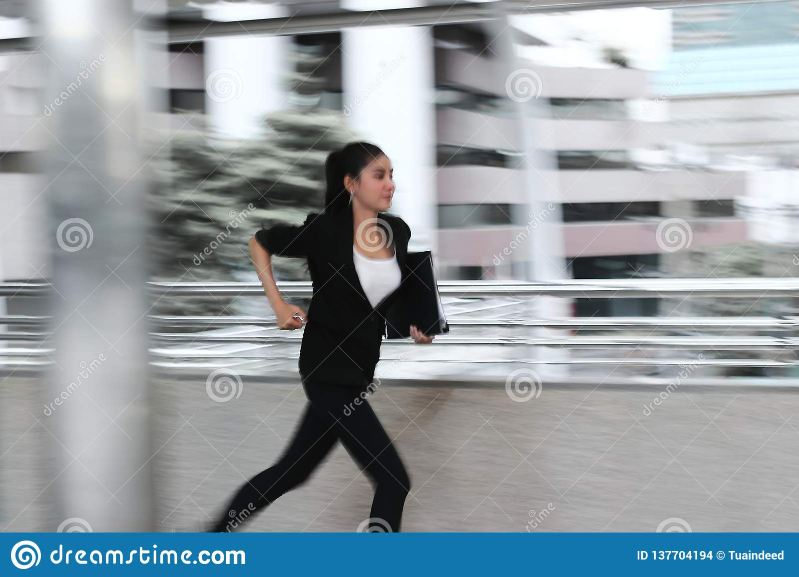 Abstract blurred motion of young Asian business woma running to work