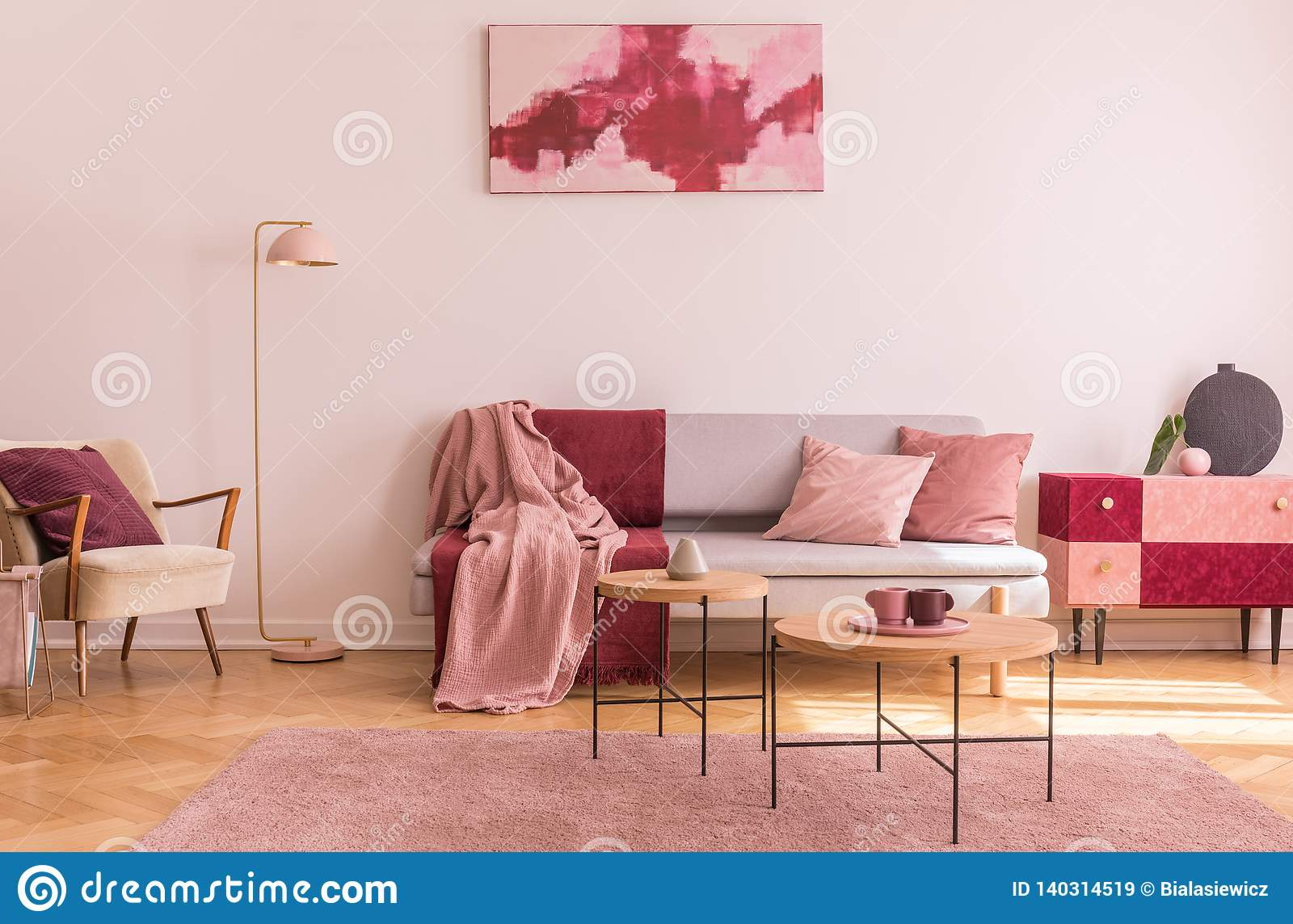 Abstract burgundy and pastel pink painting on empty white wall of fashionable living room interior with classy armchair and