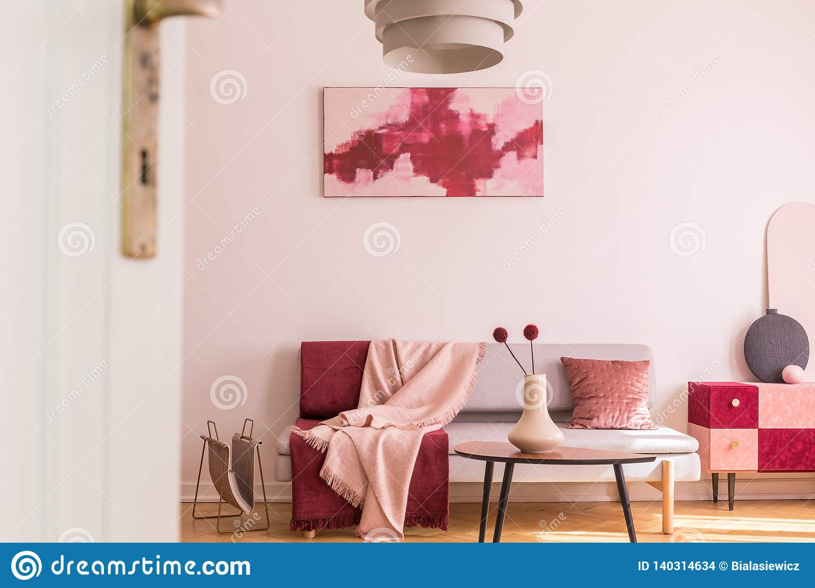 Abstract burgundy and pastel pink painting on empty white wall of trendy living room interior with grey sofa and cabinet