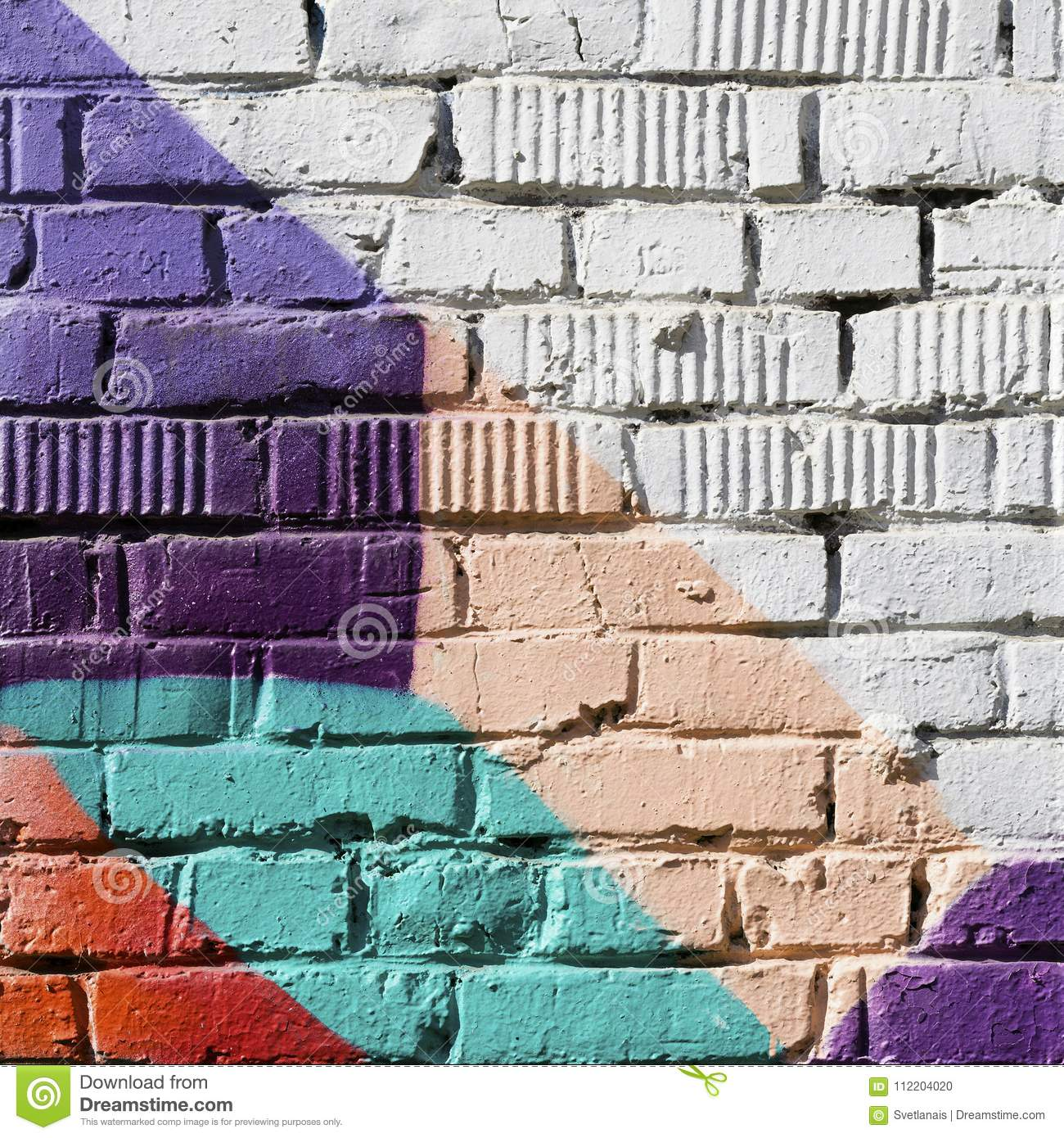 Abstract detail of brick wall with fragment of colorful graffiti. Urban Art close-up. With place for your text, for