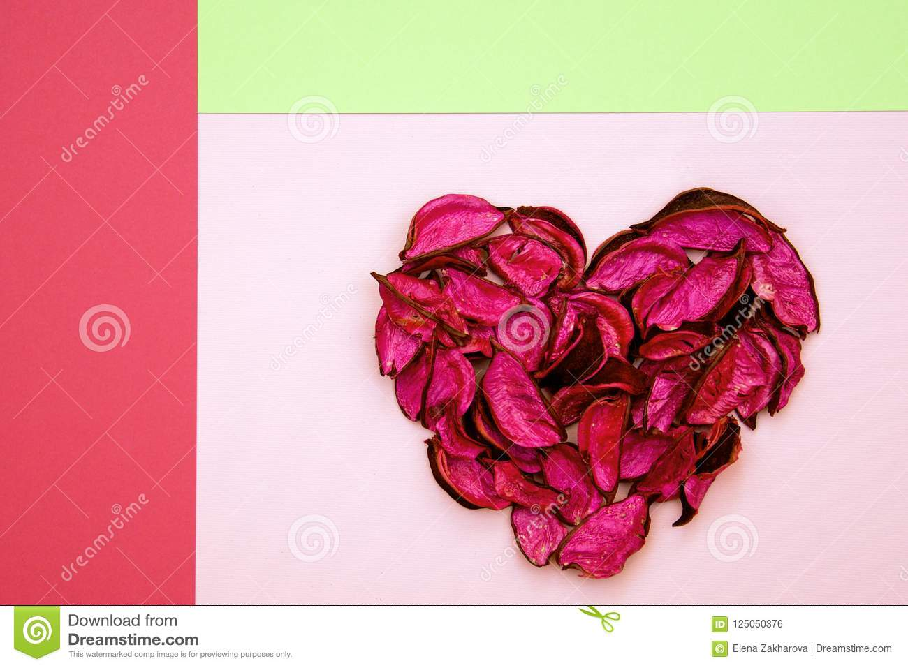 Abstract heart made of dried petals on colorful geometric background